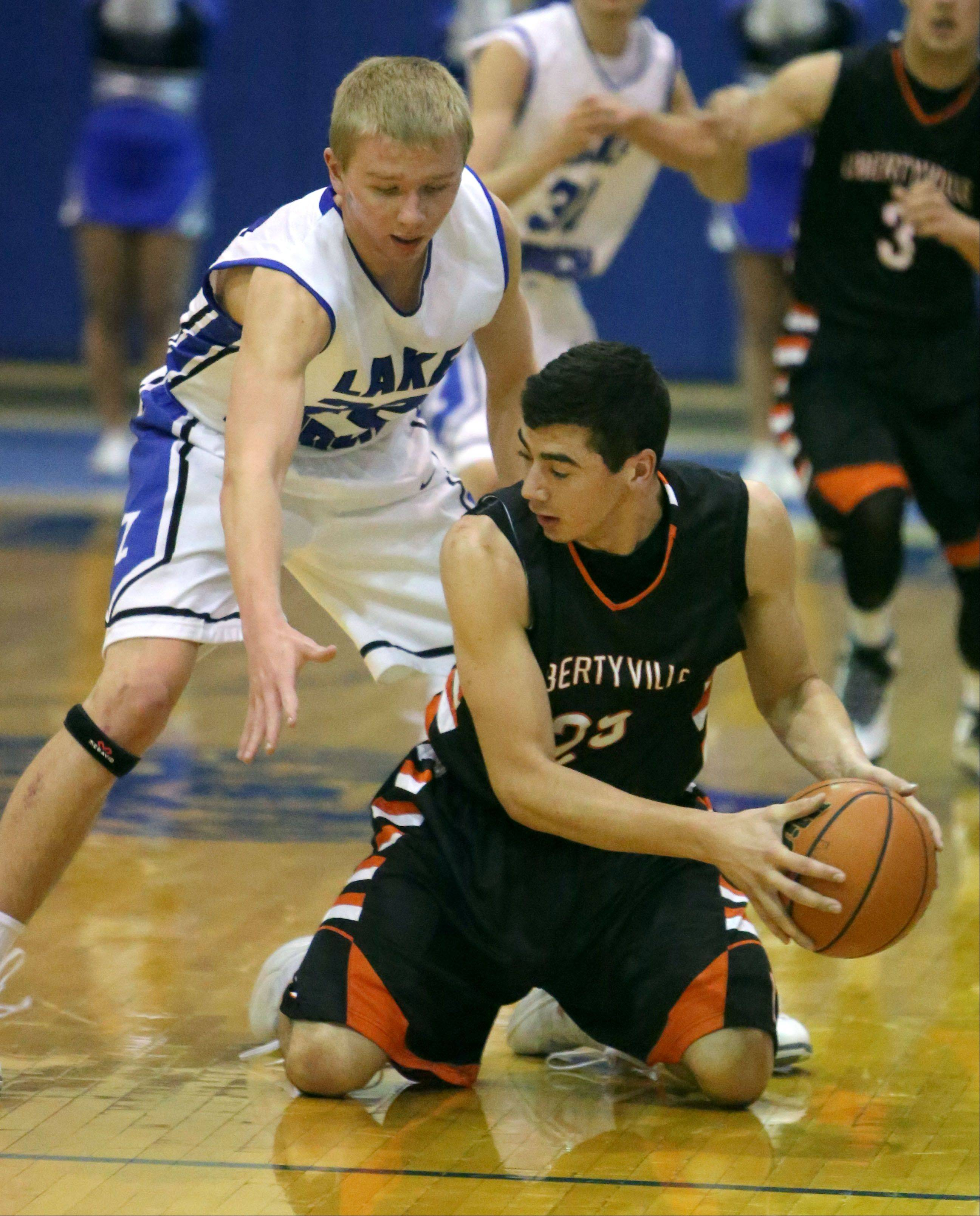 Lake Zurich's Brad Kruse, left, and Libertyville's Johnny Vernasco chase a loose ball during NSC Lake play at Lake Zurich.