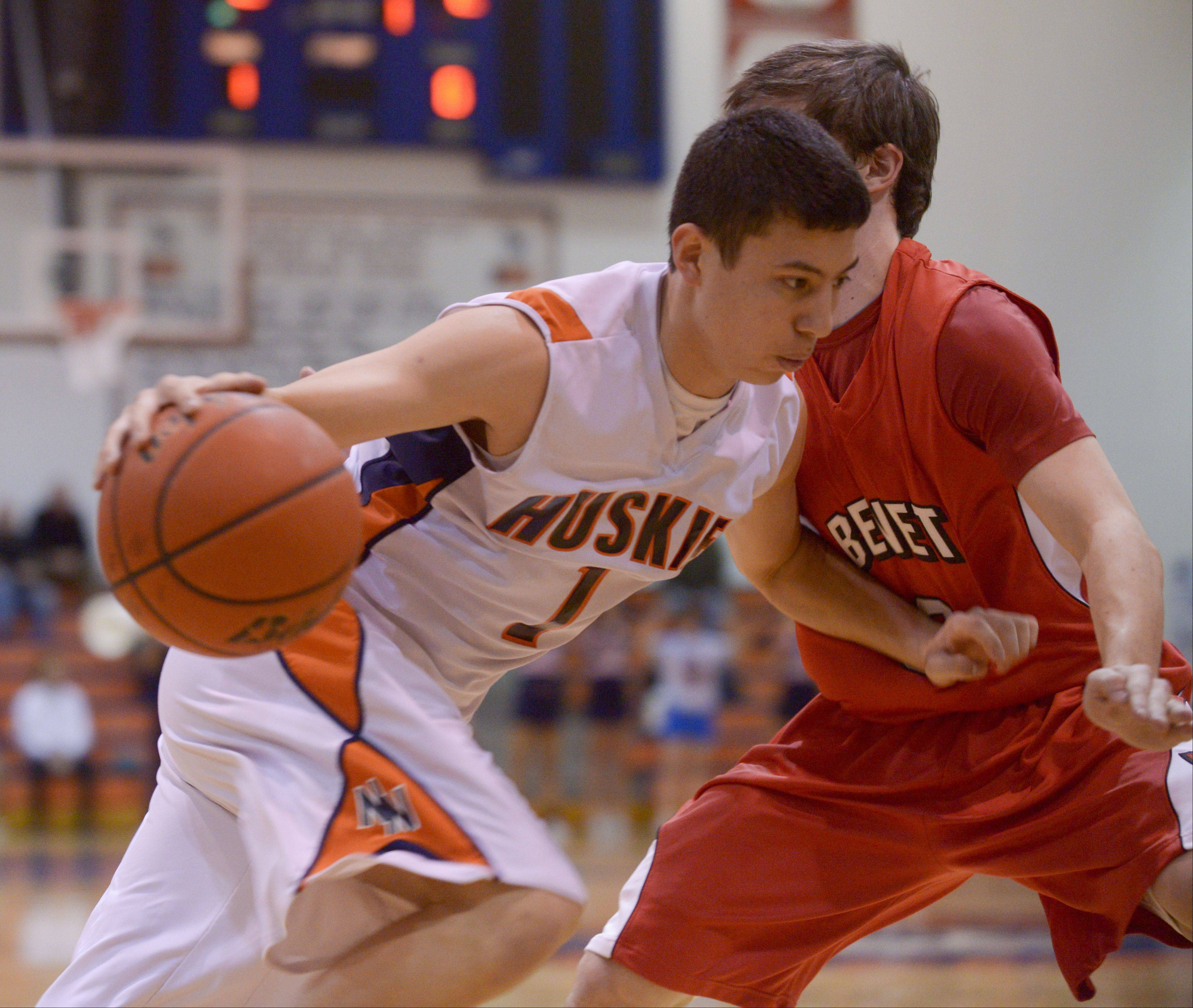 Naperville North's Jayson Winick drives around Benet's Collin Pellettieri during in boys basketball in Naperville Sunday.