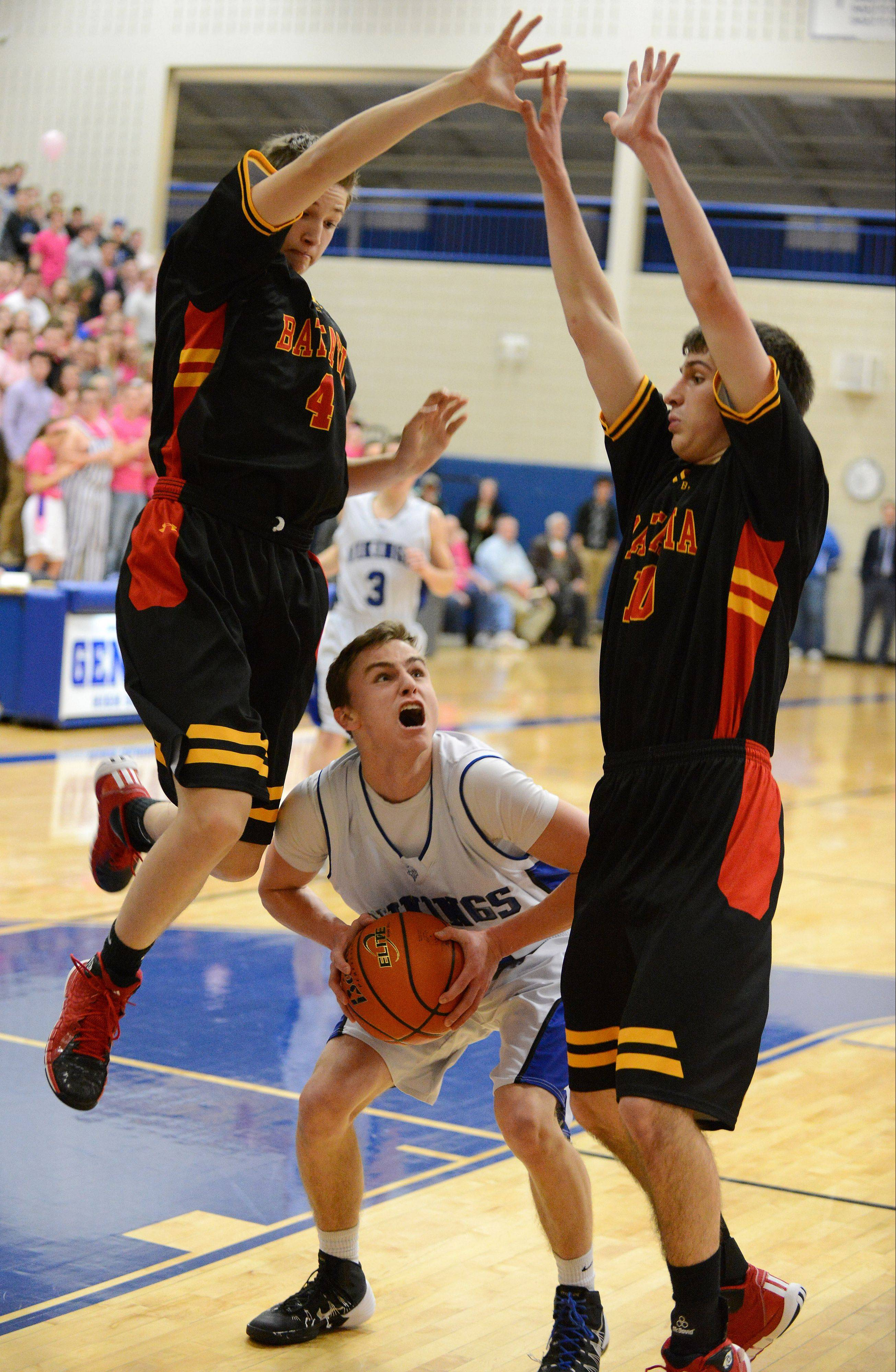 Geenva's Cam Cook pump fakes to get Batavia defenders Jacob Roberts (4) and Danny Pieczynski out of his path Friday.