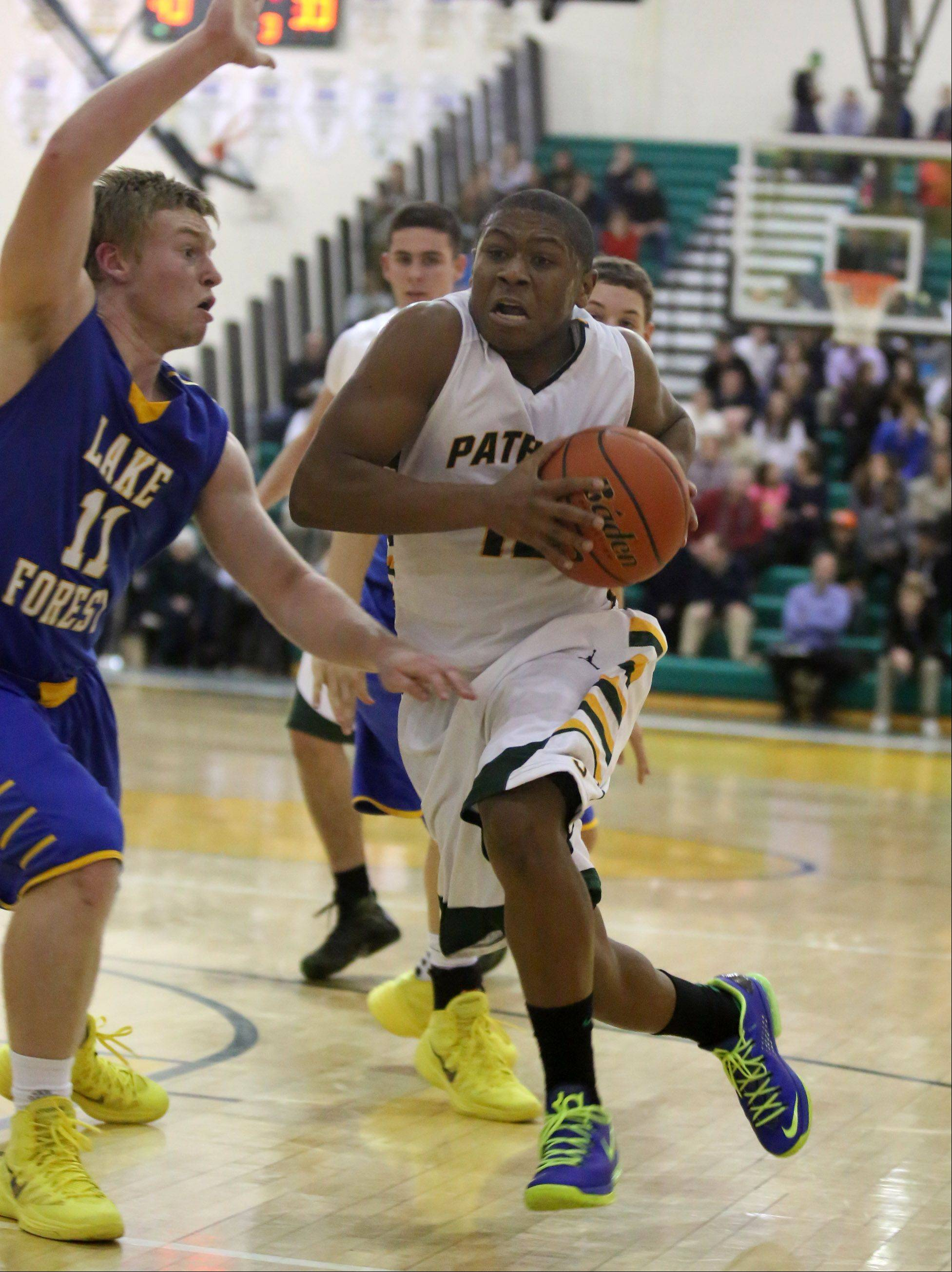 Stevenson forward Matt Johnson drives to the basket against Lake Forest defender Jack Traynor at Stevenson on Friday.