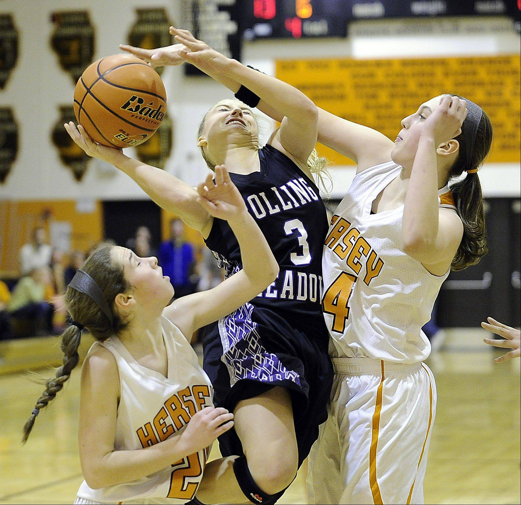 Rolling Meadows' Jackie Kemph powers her way through Hersey's defense comprised Kelly Weyhrich and Maggie Berigan in girls basketball at Hersey.