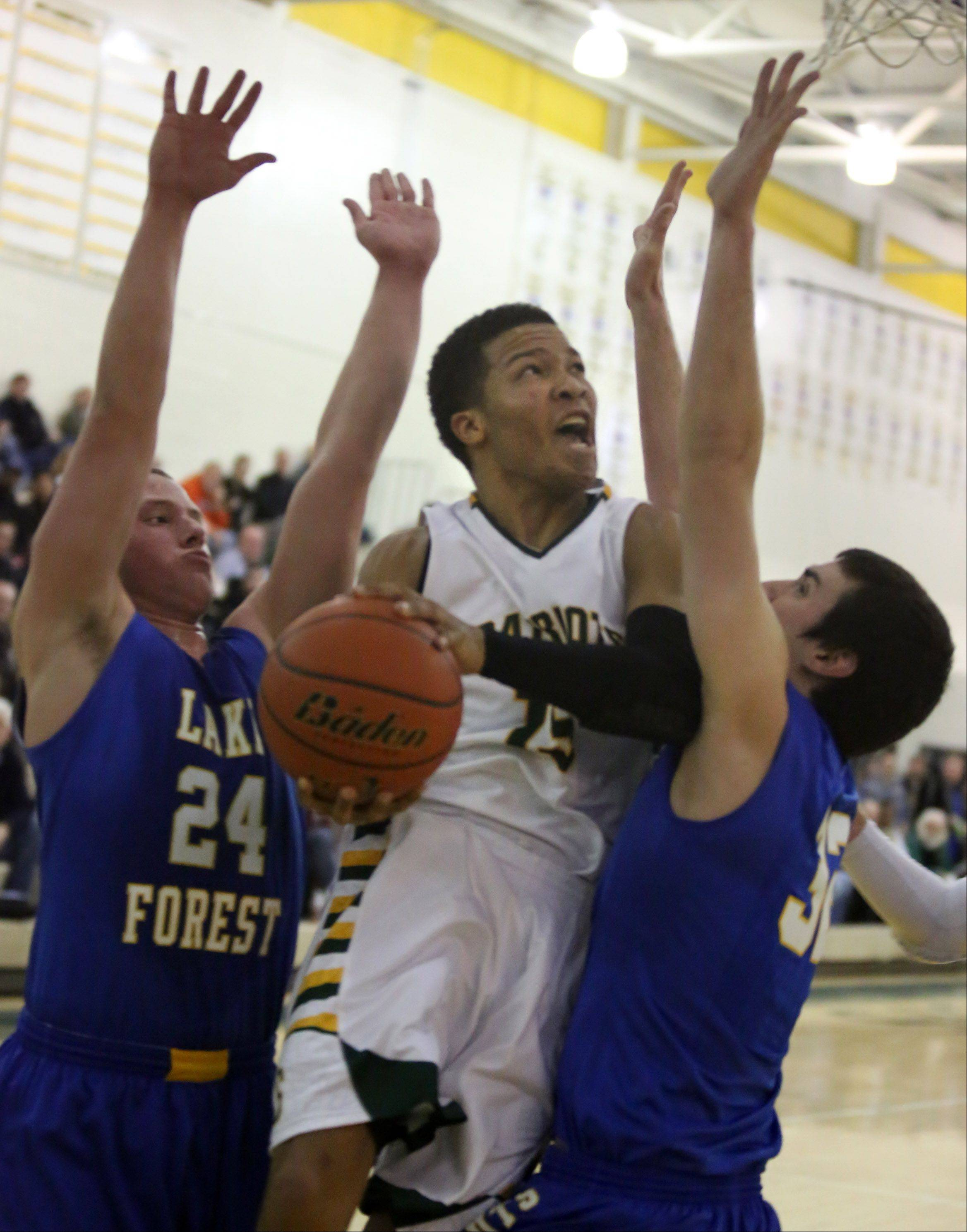Stevenson forward Justin Smith puts the ball while sandwiched between two Lake Forest defenders including Cal Miller, left, at Stevenson on Friday in Lincolnshire.