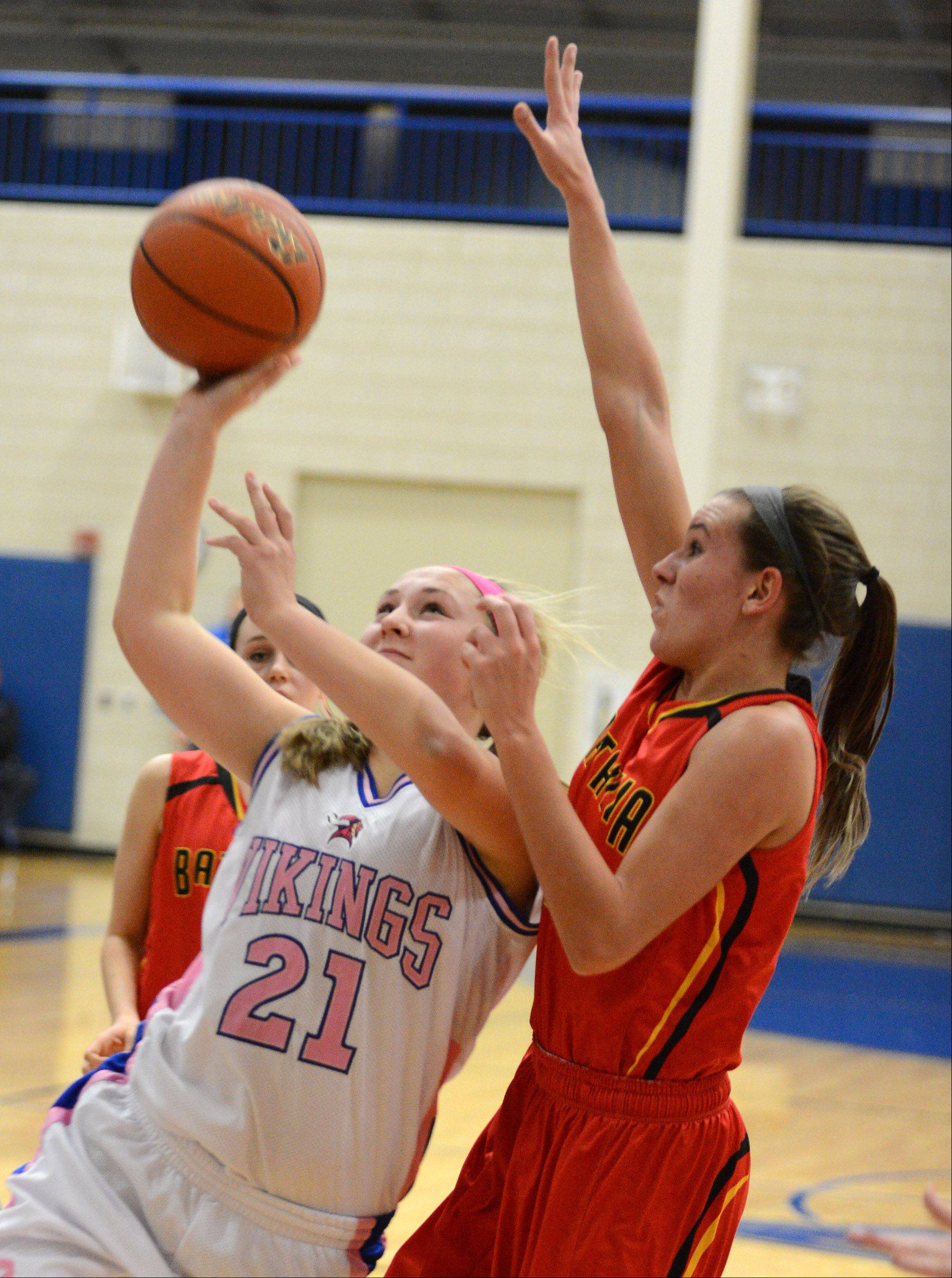 Geneva's Taylor Williams (21) drives to the basket with Batavia's Liza Fruendt (5) defending during Friday's game in Geneva.