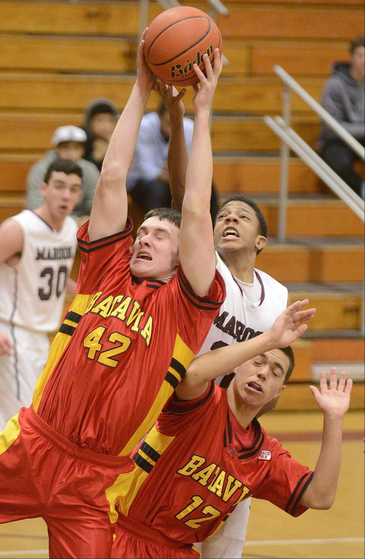 Batavia's Ryan Olson (42) and Elgin's Donte Harper leap for a rebound over Batavia's Canaan Coffey (12) in the second quarter on Saturday, January 18.