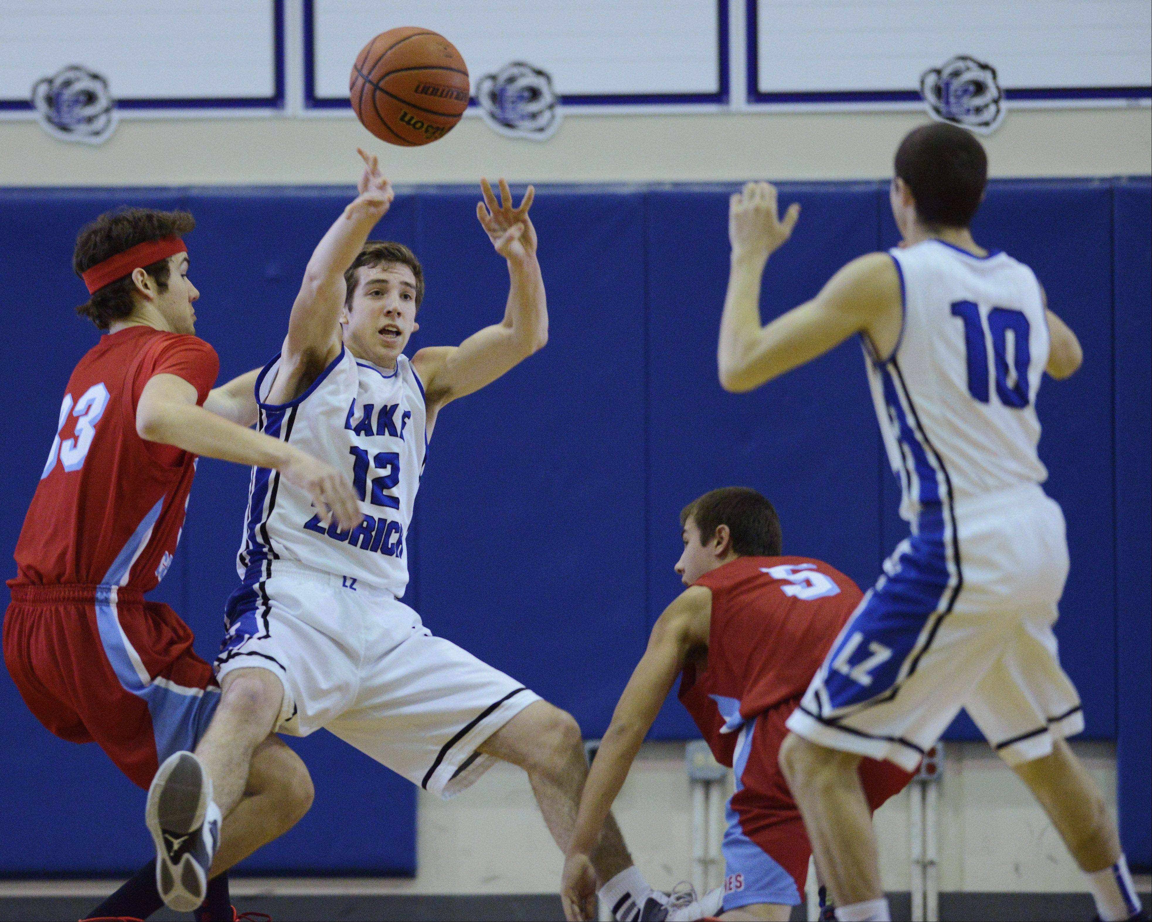 Lake Zurich's Corey Helgeson, second from left, passes the ball to teammate Dave Brown, right, after grabbing a loose ball between Marian Central's Quinn Haley, left, and Adam Pischke during the Martin Luther King Classic at Lake Zurich Saturday.