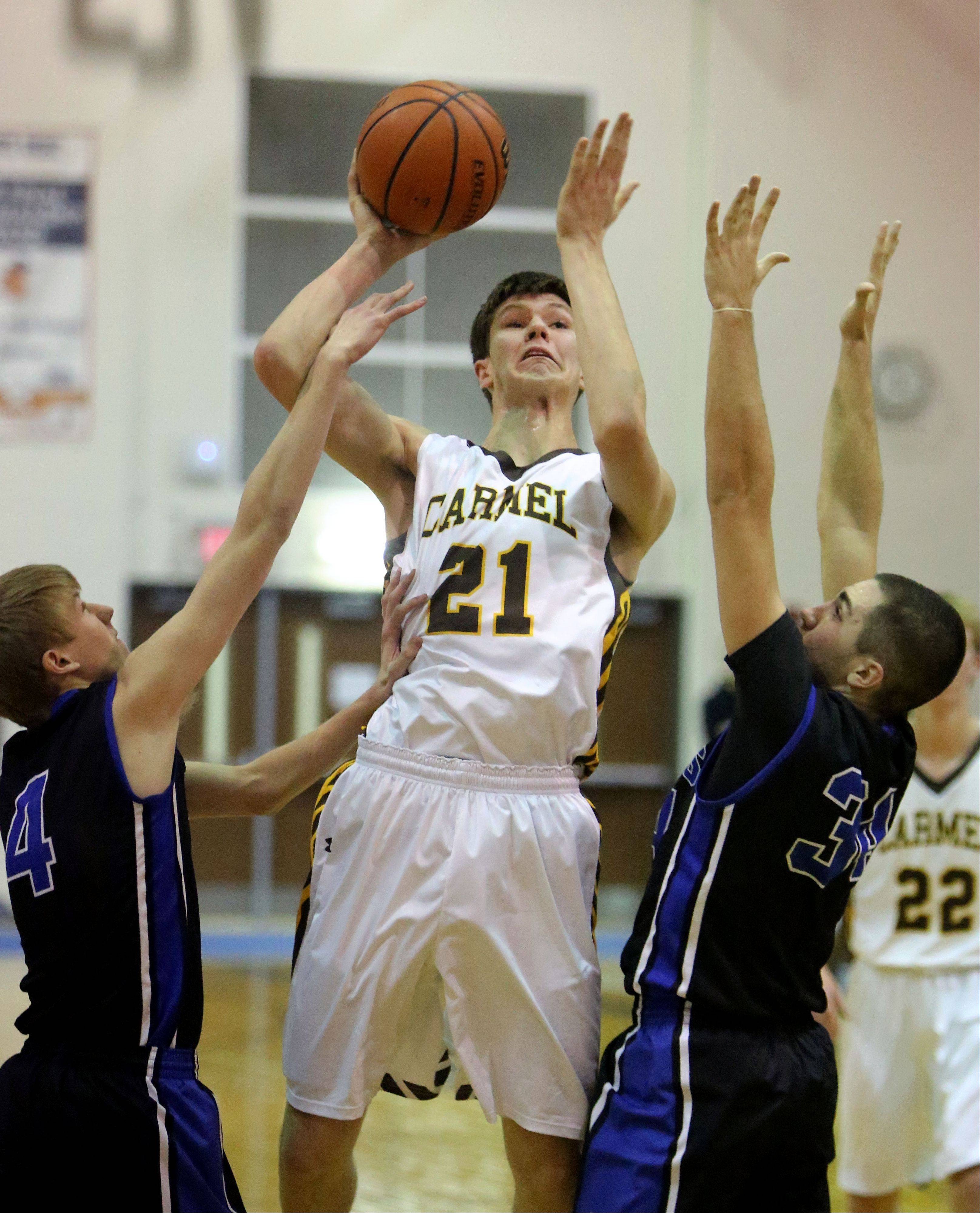 Carmel's Jack George (21) drives on Lake Zurich's Jeff Zahery, left, and Mike Travlos on Monday at Lake Zurich.
