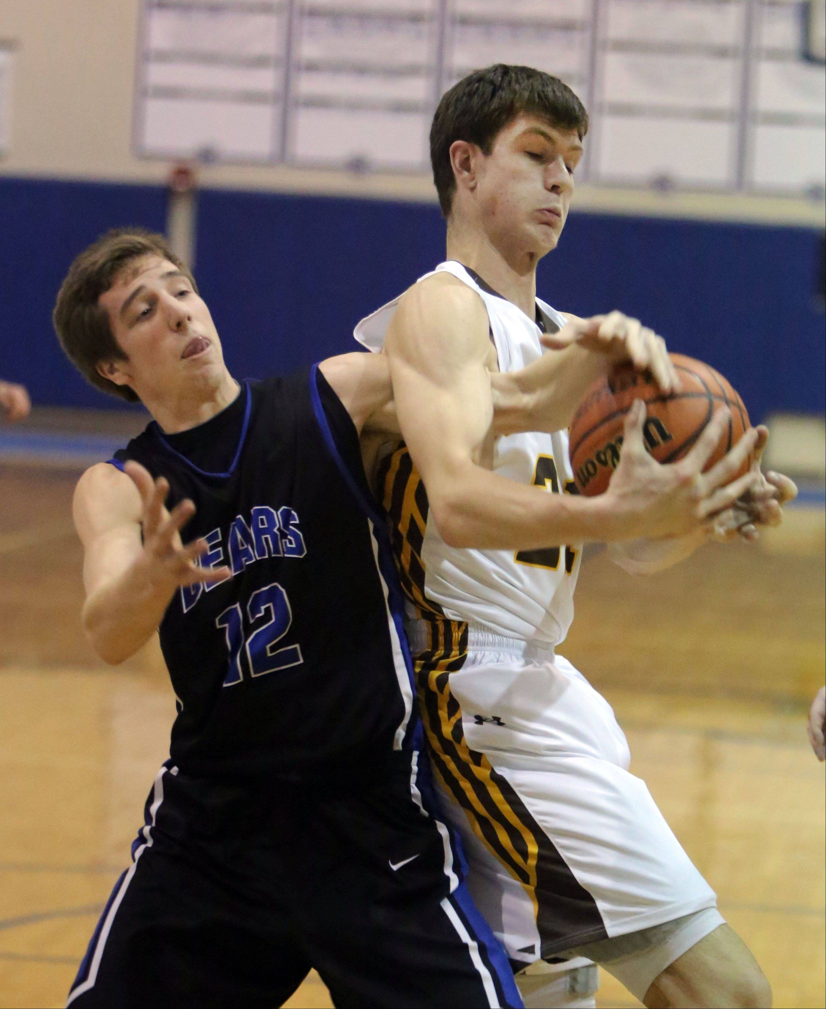 Lake Zurich's Corey Helgeson, left, and Carmel's Jack George battle for a rebound Monday at Lake Zurich.