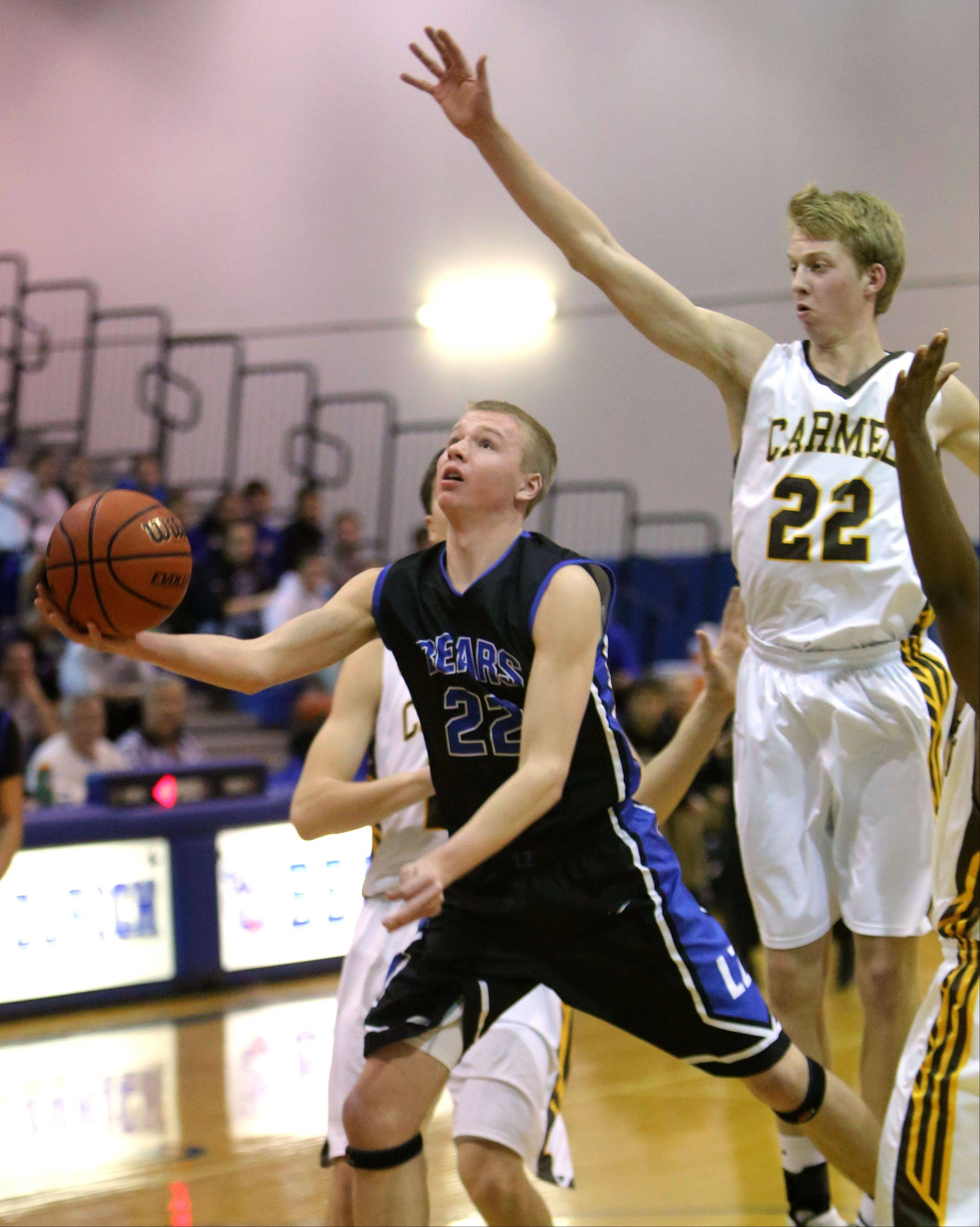 Lake Zurich's Brad Kruse, left, drives to the hoop past Carmel's Michael Barr on Monday at Lake Zurich.
