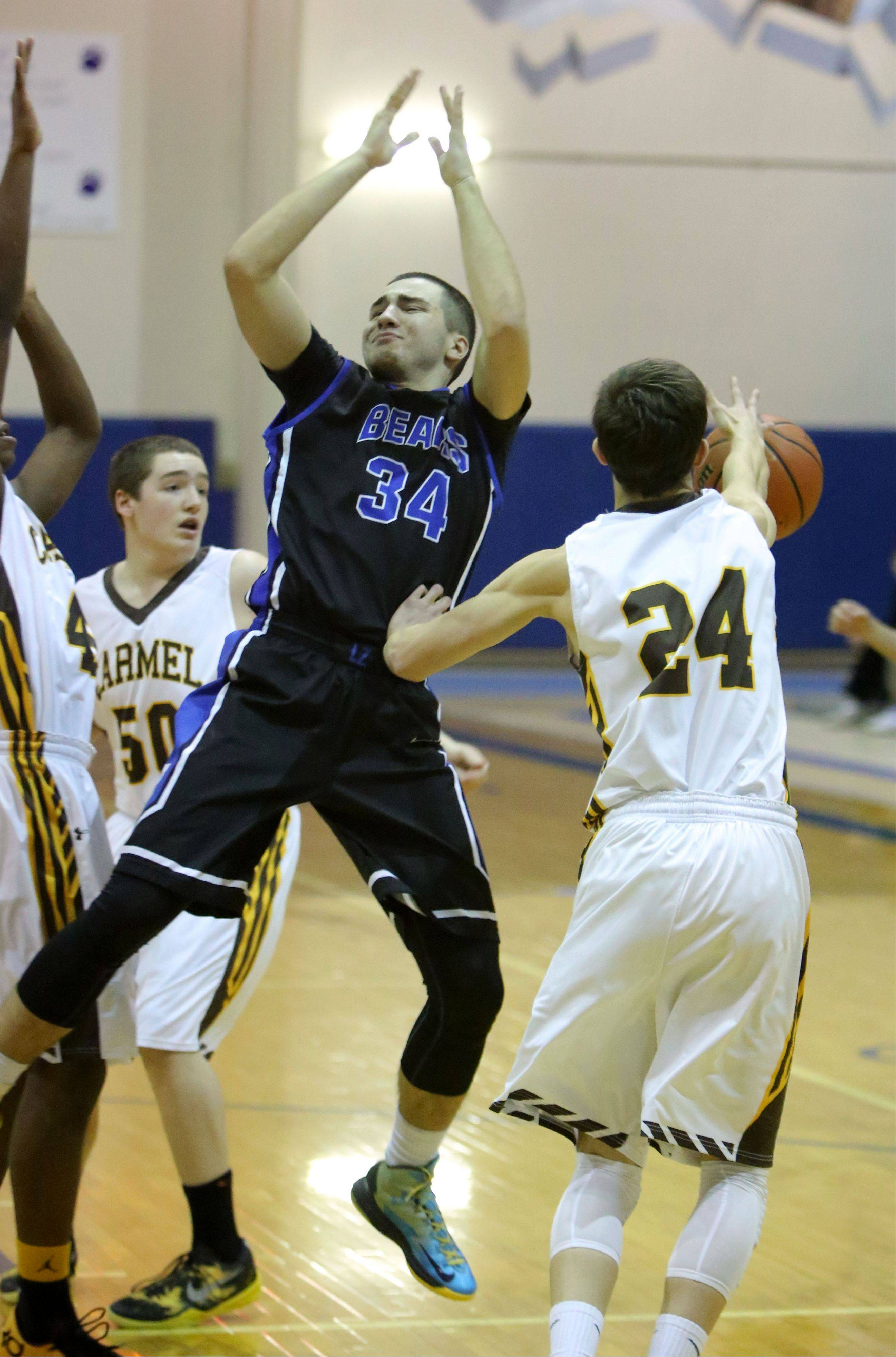 Lake Zurich's Mike Travlos (34) gets his shot blocked by Carmel's Billy Kirby on Monday at Lake Zurich.