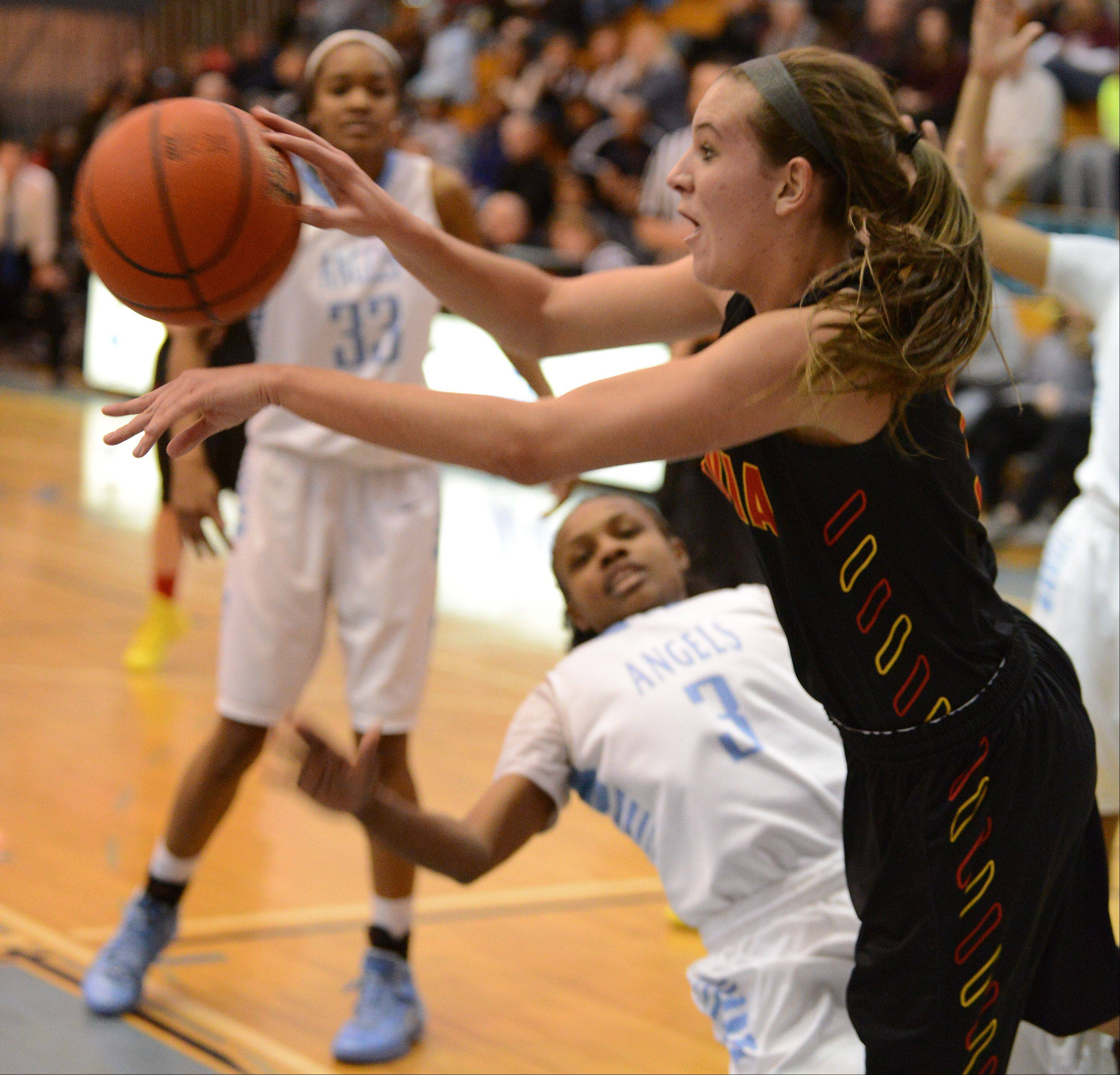 Batavia's Liza Fruendt dishes off after driving along the baseline against Joliet Catholic during Monday's game at the 24th annual McDonald's Shootout at Willowbrook High School in Villa Park.