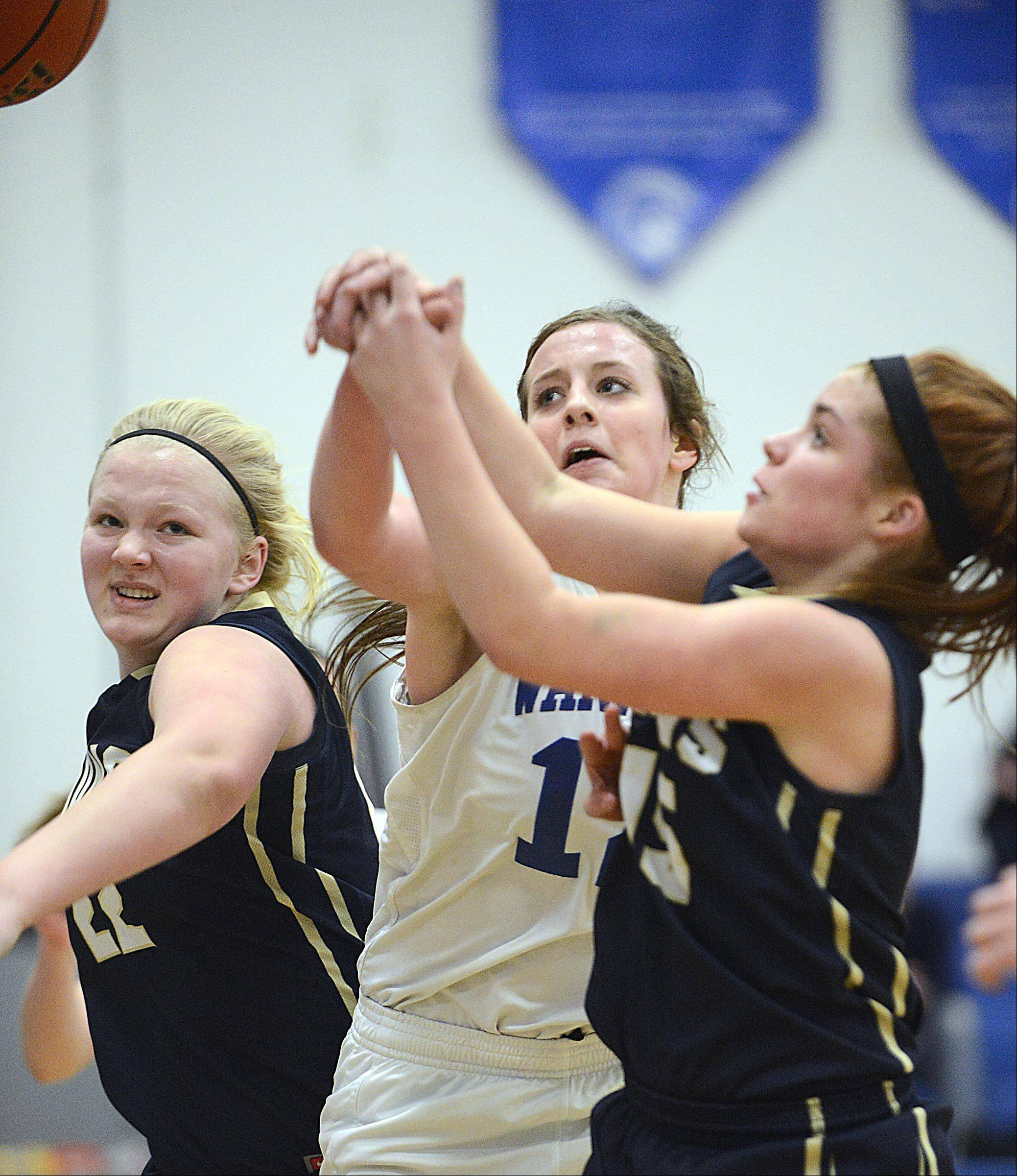 Harvest Christian's Rachel Oostdyk, left, and Hannah Hendricks fight for a rebound with Westminster Christian's Maddie Versluys Monday in Elgin.