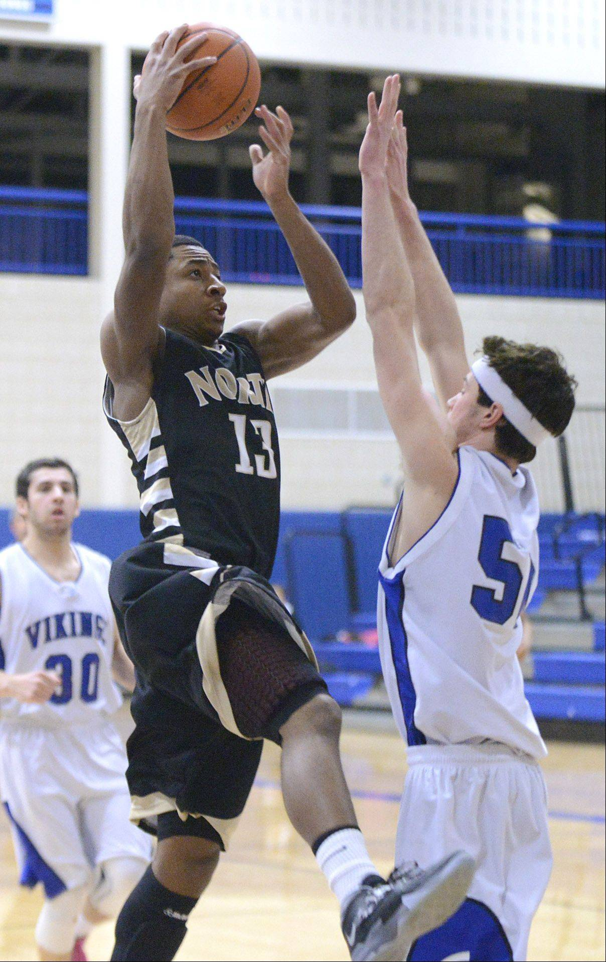 Glenbard North's Justin Jackson shoots over a block by Geneva's Mike Landi in the first quarter on Tuesday, January 21.