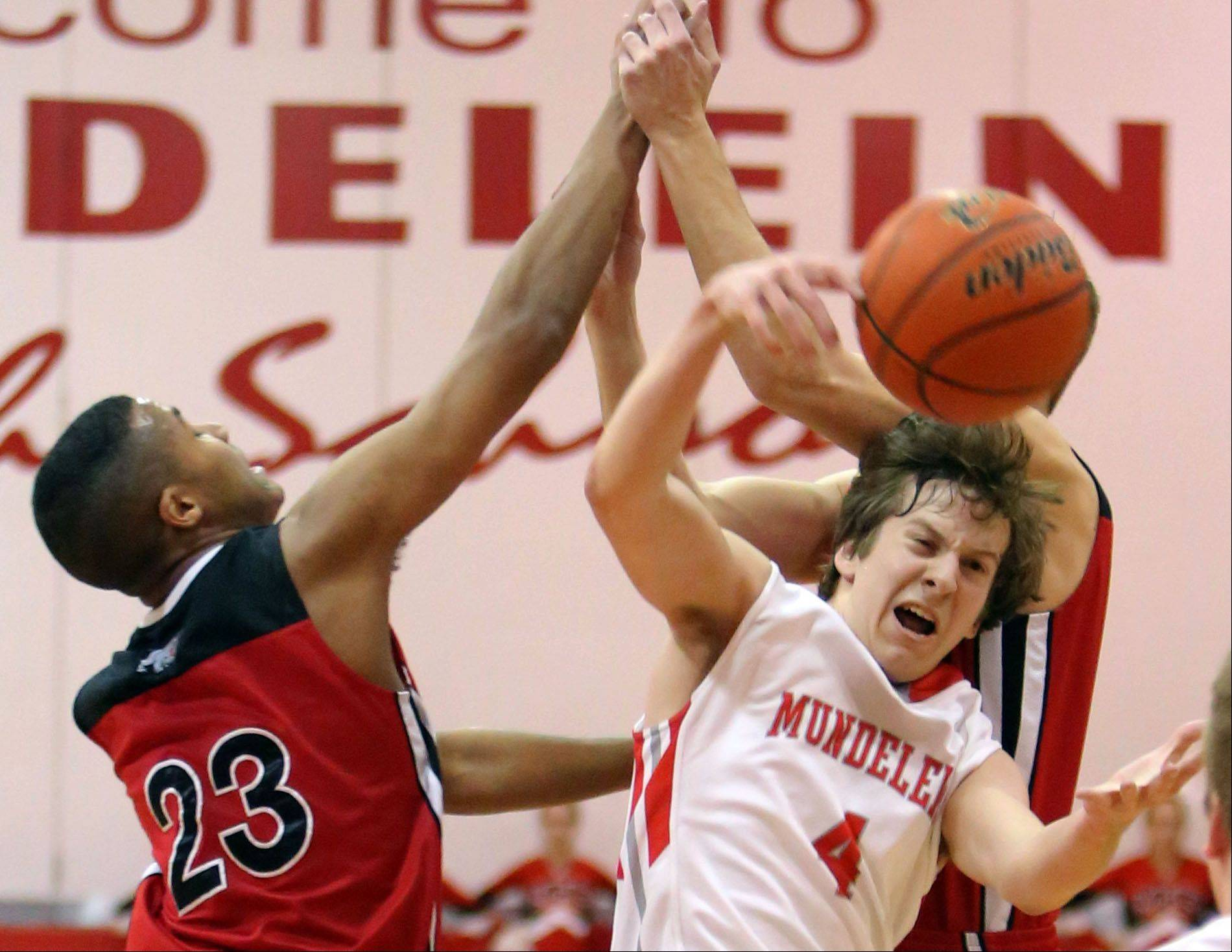 Grant's Steve Dunning, left and Mundelein's Sam Nelson fight for a loose ball on Tuesday at Mundelein.