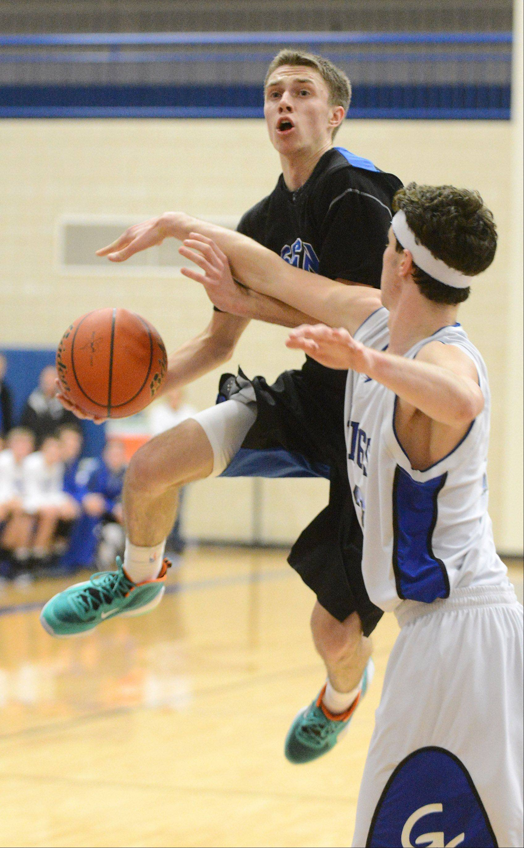 St. Charles North's Alec Goetz (1) drives to the basket as he is defended by Geneva's Mike Landi (52) during Friday's game in Geneva. ¬