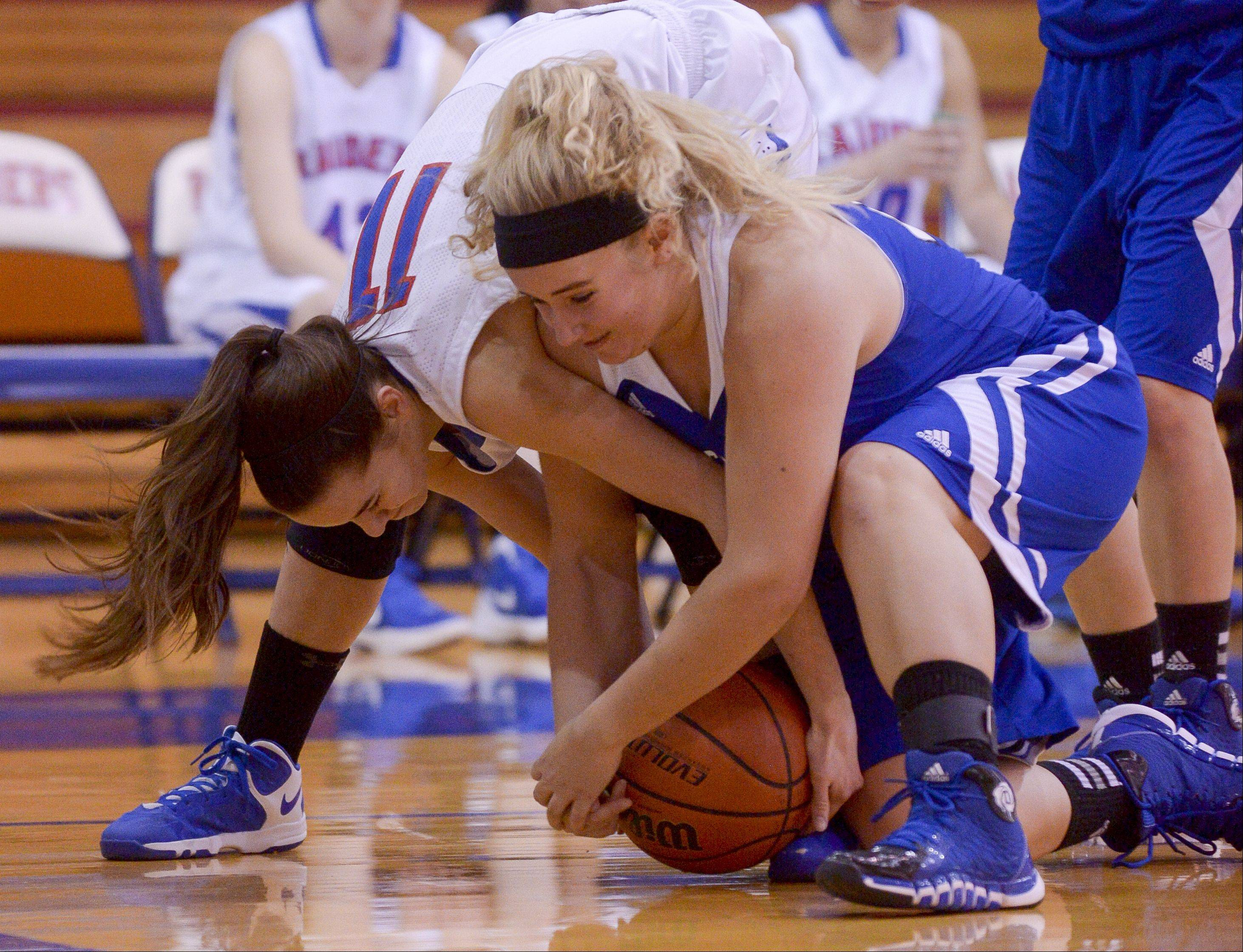 Glenbard South's Jenna Brambora and St. Francis's Danielle Ament struggle for control of the ball.