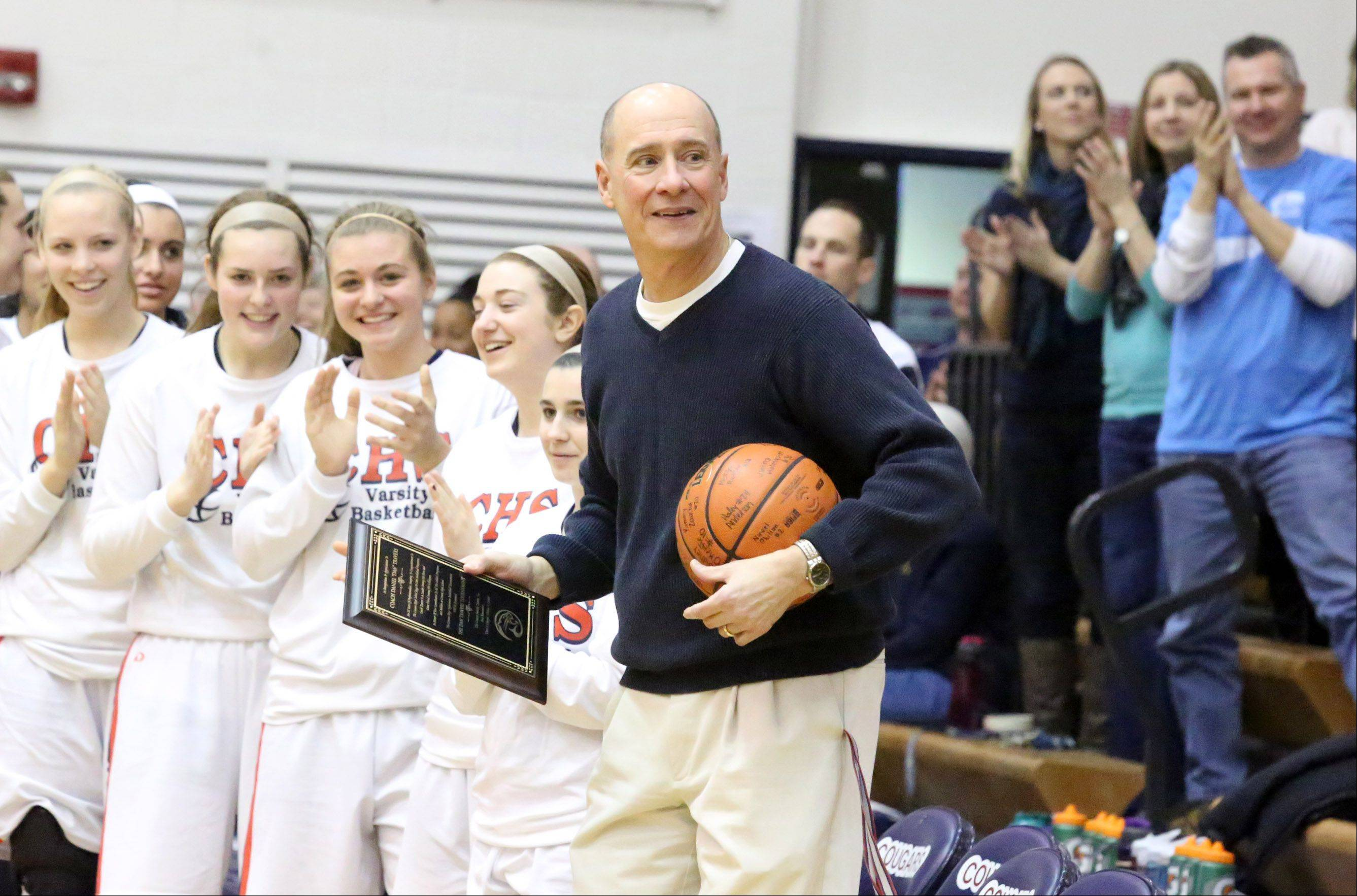Conant girls basketball coach Dan Travers receives a standing ovation from his players and fans after receiving a plaque from athletic director John Kane on Saturday before a game with Crystal Lake South at Conant. Travers has coached high school basketball for 38 years.