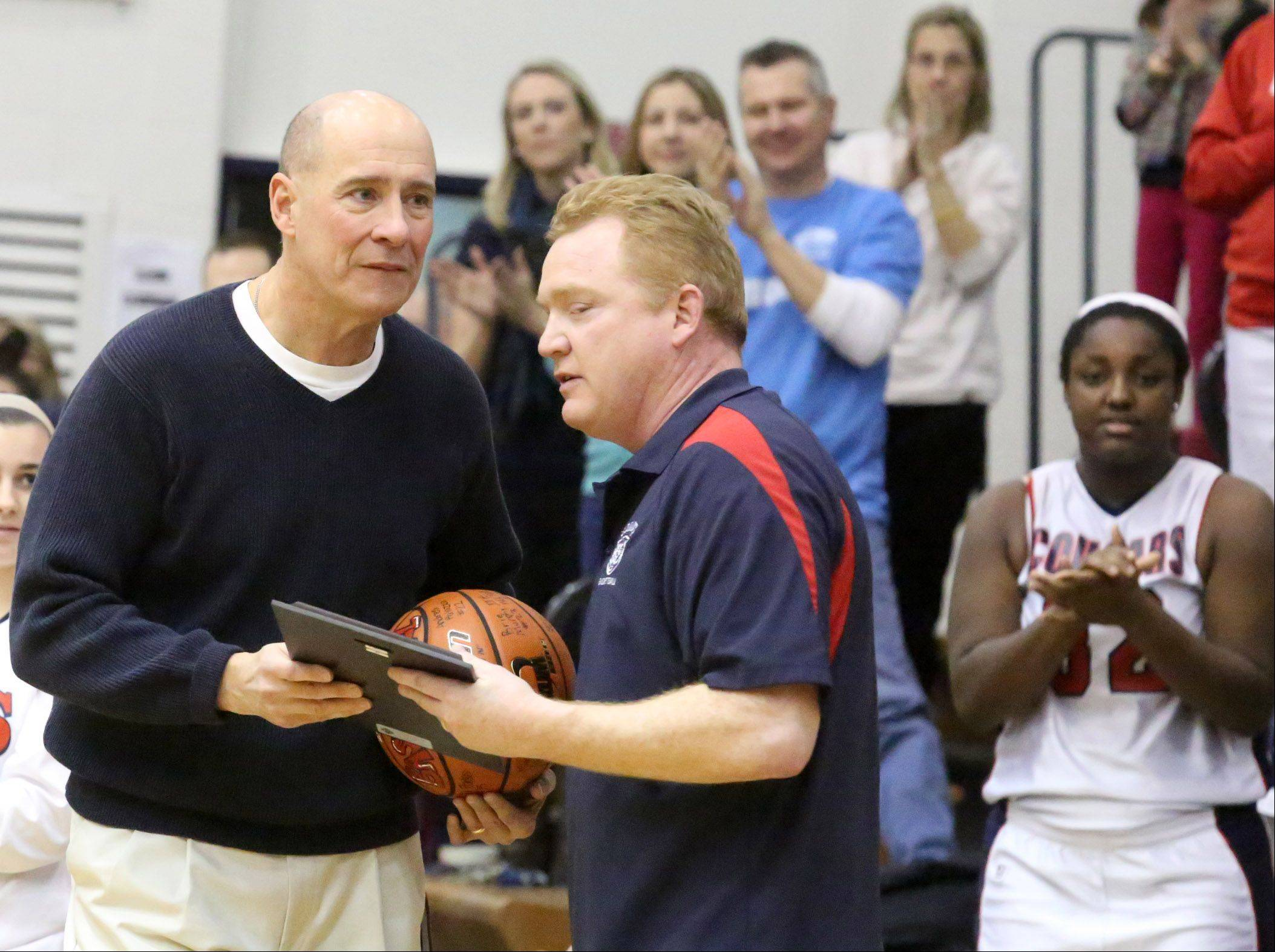 Conant girls basketball coach Dan Travers receives a plaque from athletic director John Kane on Saturday before a game with Crystal Lake South at Conant. Travers has coached high school basketball for 38 years.