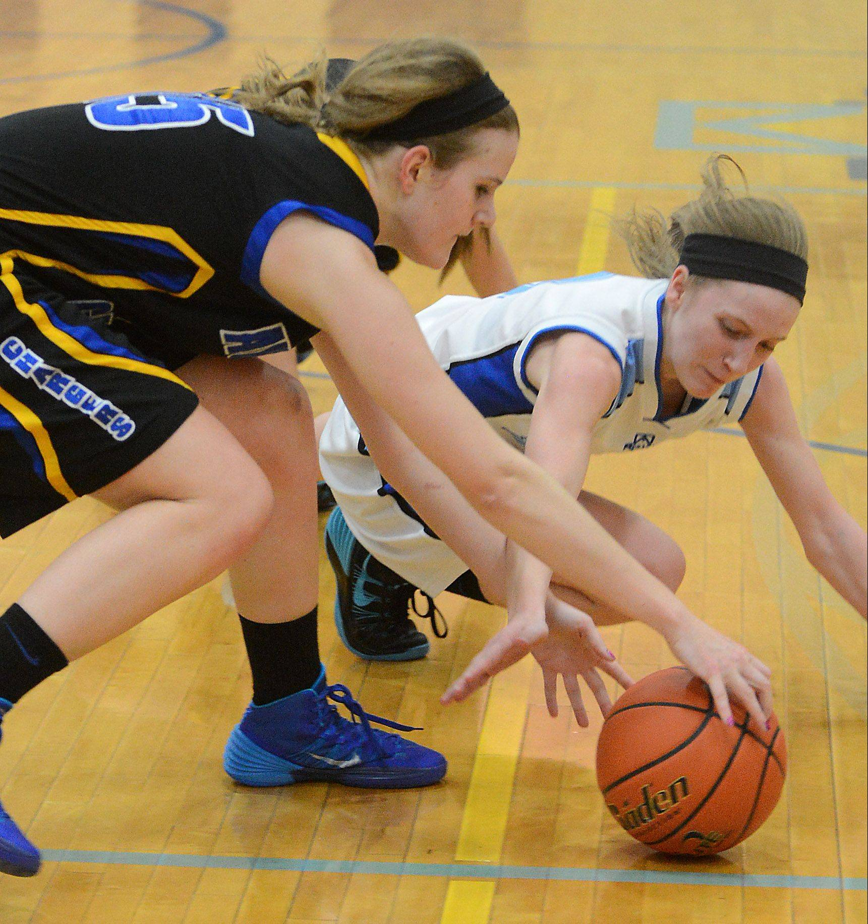 This is the kind of hustle Rosary coach Jessie Wilcox has come to expect from Rachel Choice, right, diving for a loose ball against Aurora Central Catholic's Natalie Droeske.