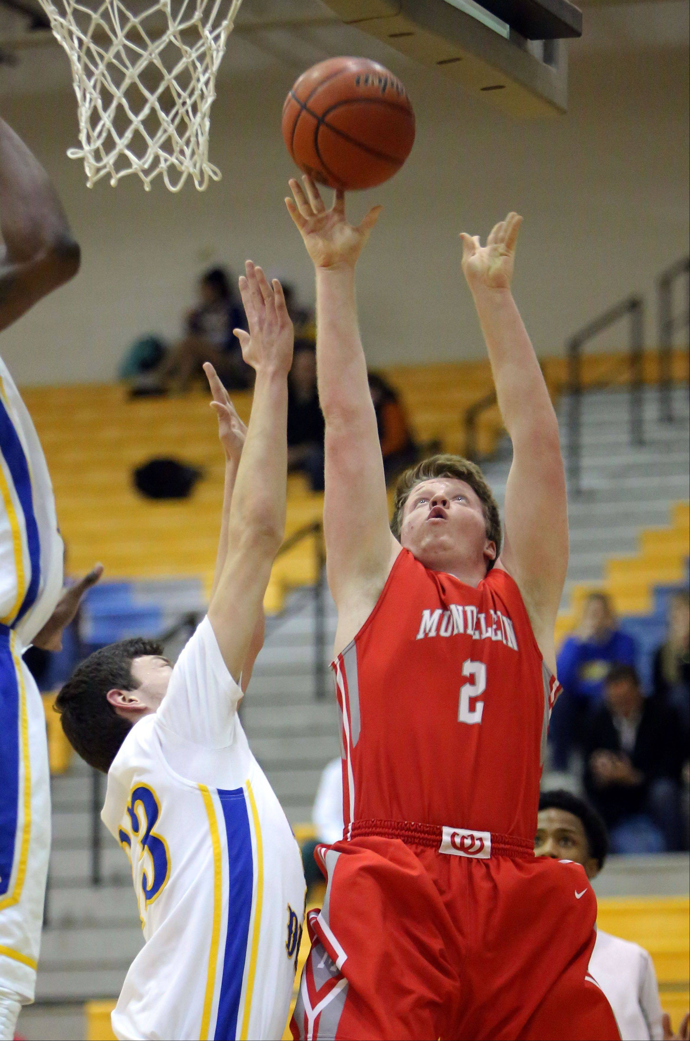 Mundelein's Kevin Marcotte, right, drives to the hoop on Warren's Jovan Jokic on Wednesday night at Warren.