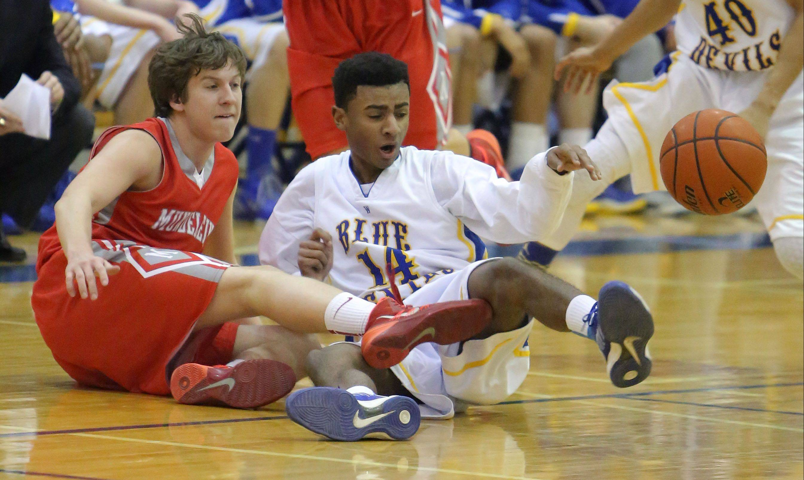 Mundelein's Sam Nelson, left, and Warren's Adrian Deere scramble for a loose ball on Wednesday night at Warren.
