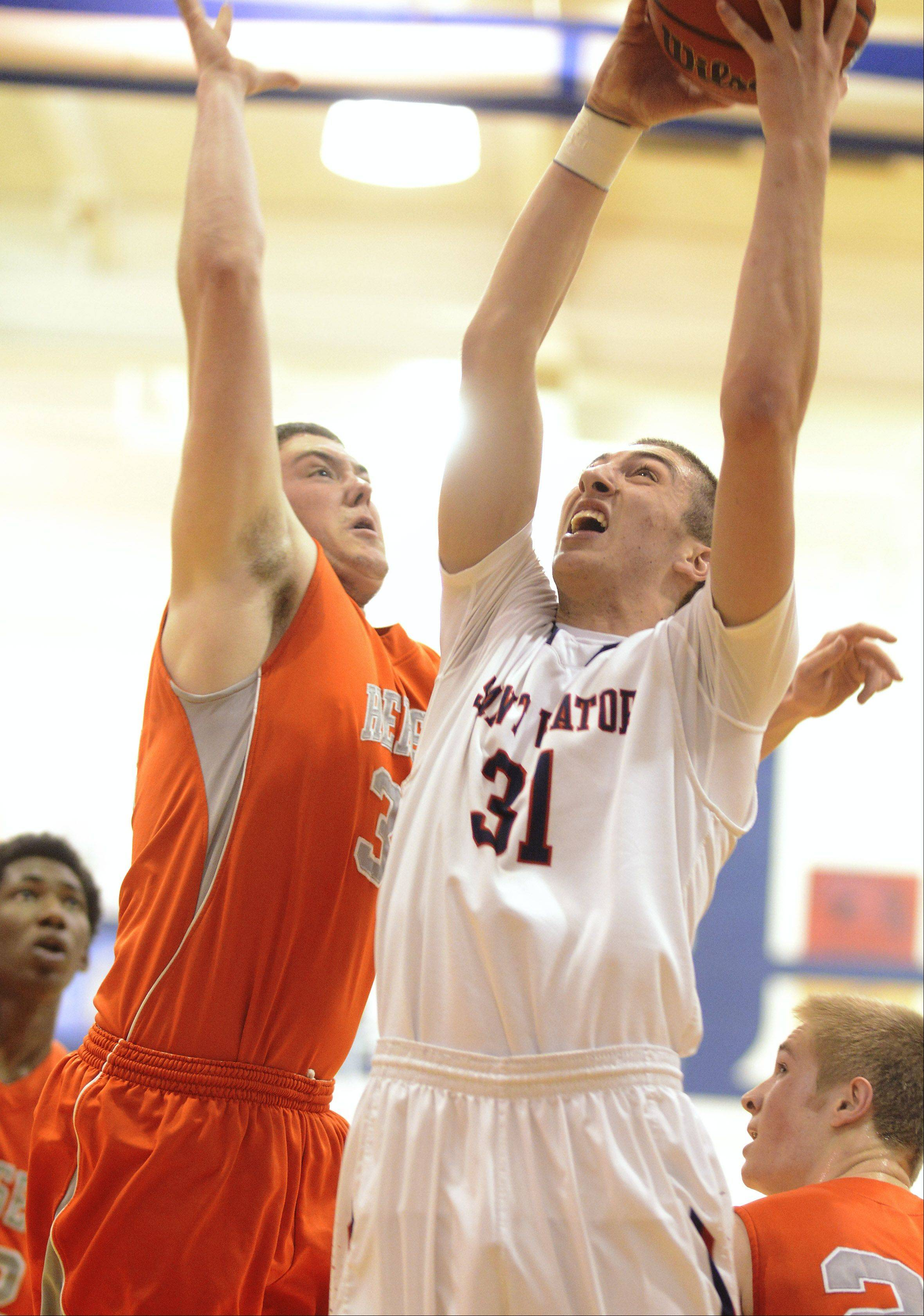St. Viator's Sal Cannella, right, makes a strong move to the basket against hersey defender Michael Messer during Wednesday's game in Cahill Gymnasium.