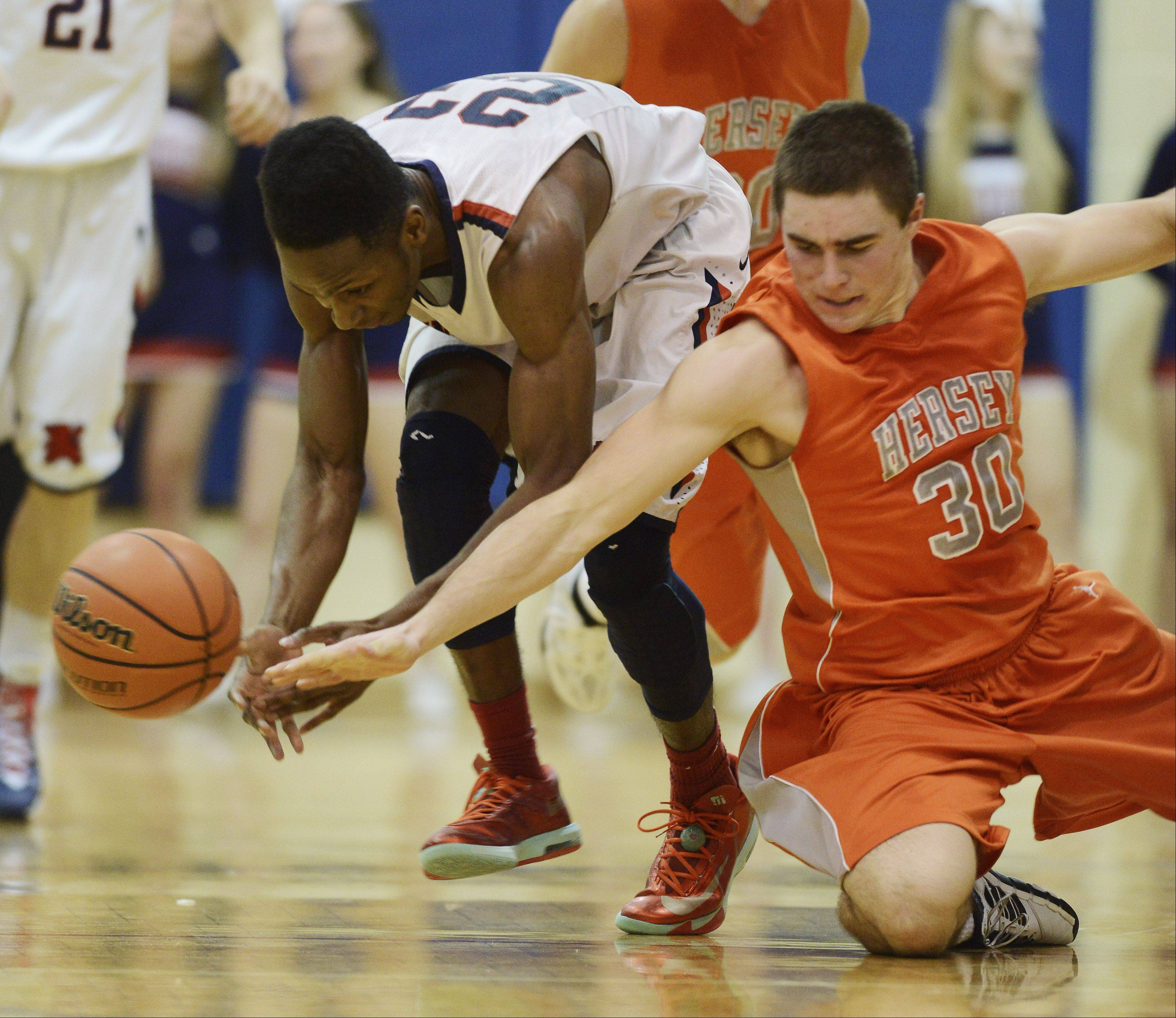 St. Viator's Ore Arogundade, left, tries to tap a loose ball away from Hersey's Grant Burke during Wednesday's game in Cahill Gymnasium.