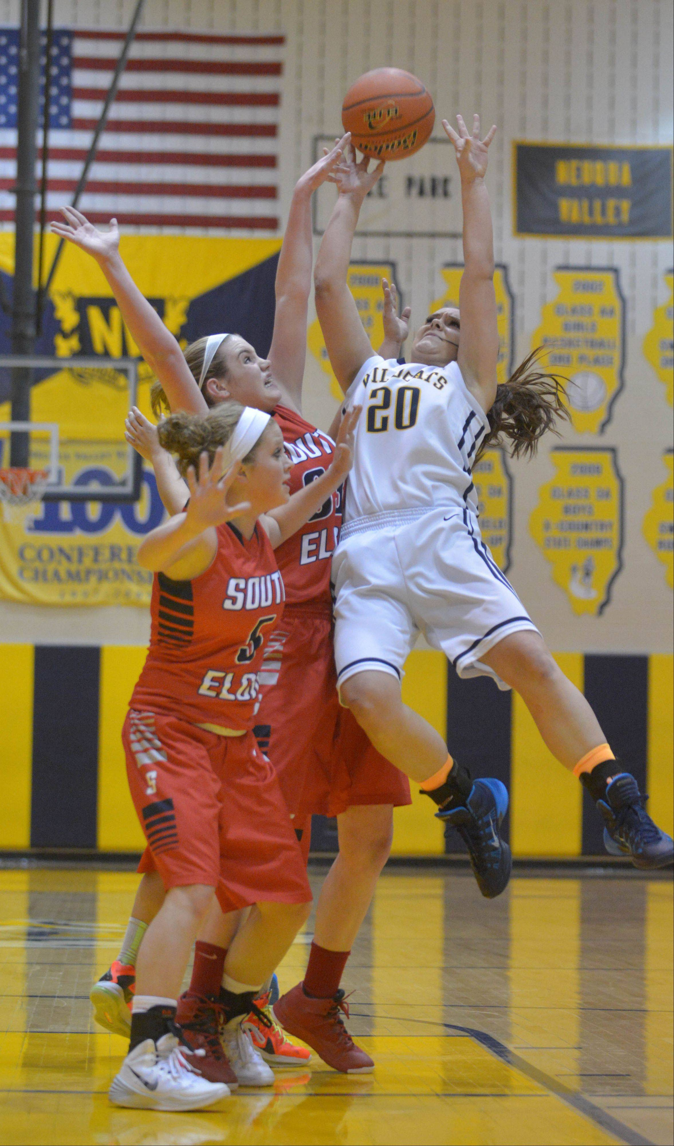 Anna Tracy and Mackie Kelleher of South Elgin go for a rebound with Niki Lazar of Neuqua Valley.