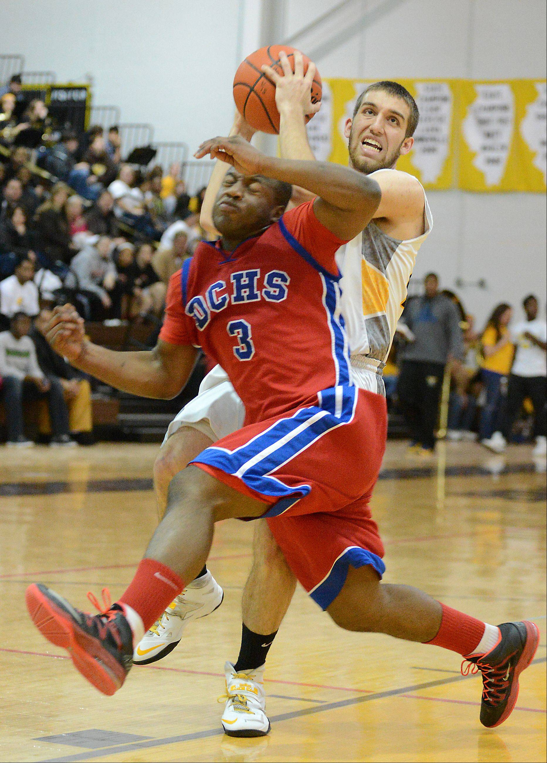 Ben Murray of Jacobs gets tangled up with Dundee-Crown's Cordero Parson before breaking free for a layup and a foul.