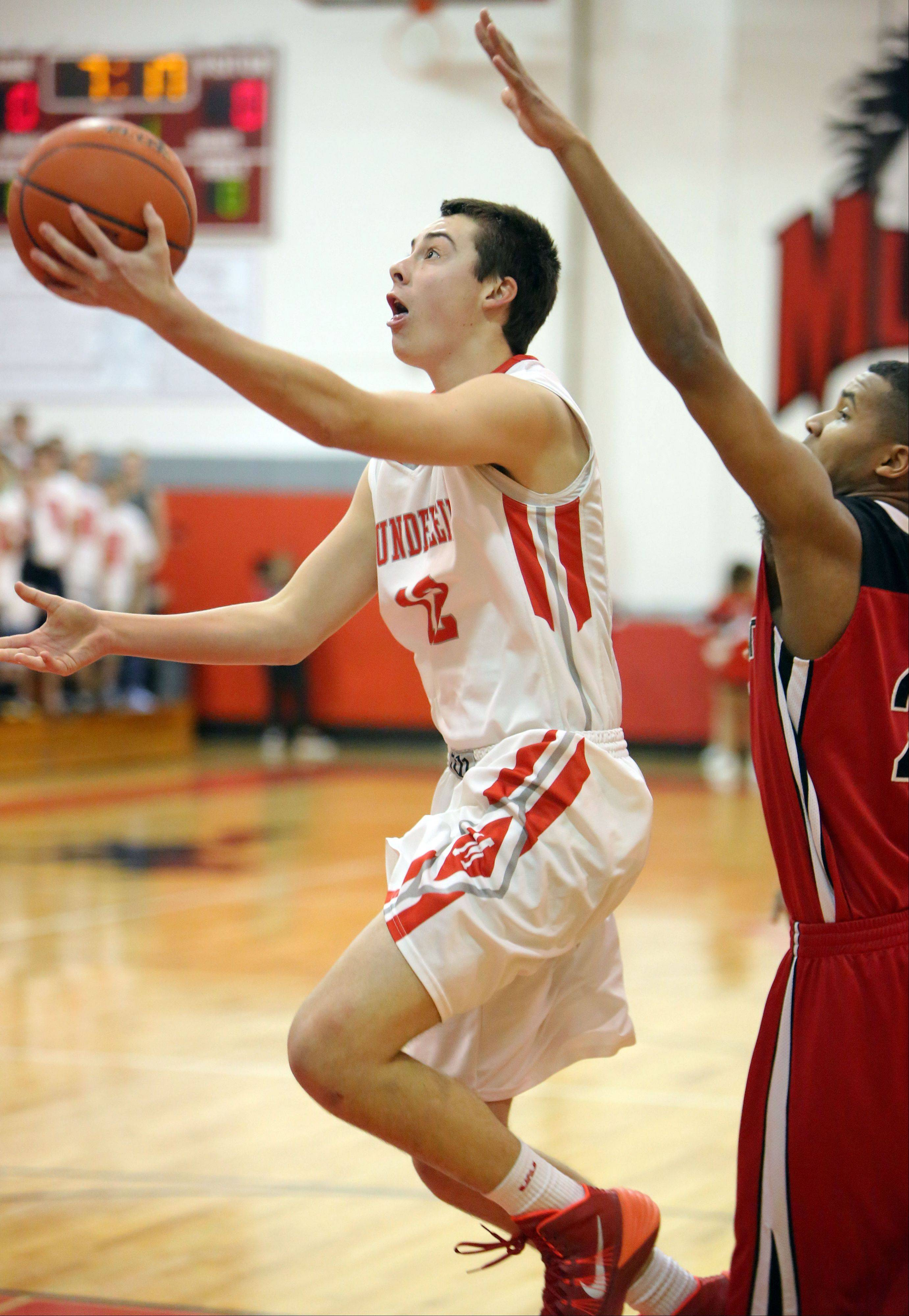 Mundelein's Derek Parola, left, drives to the hoop against Grant's Steve Dunning.