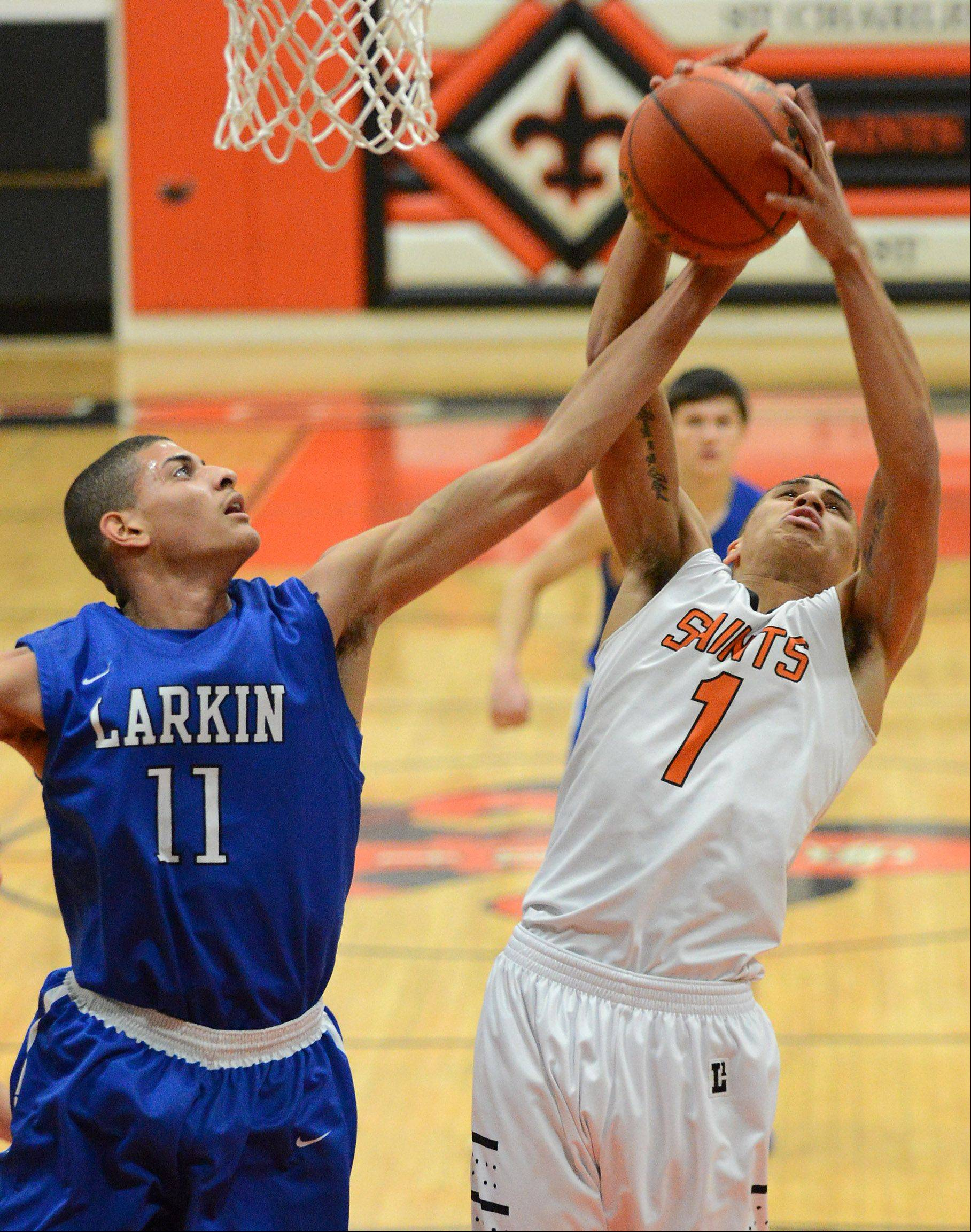 Larkin's Christian Negron (11) and St. Charles East's AJ Washington (1) battle for a rebound during Thursday's game in St. Charles.