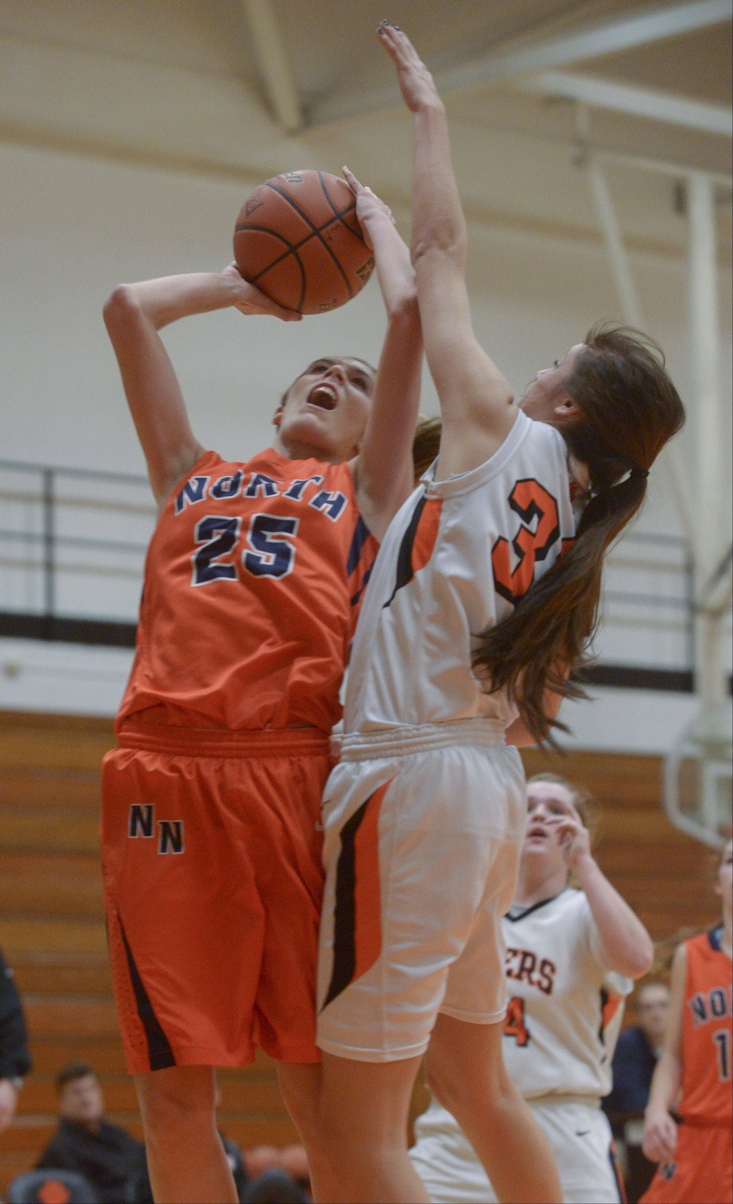 Naperville North's Kayla Sharples is fouled by Wheaton Warrenville South's Erin Zappia.