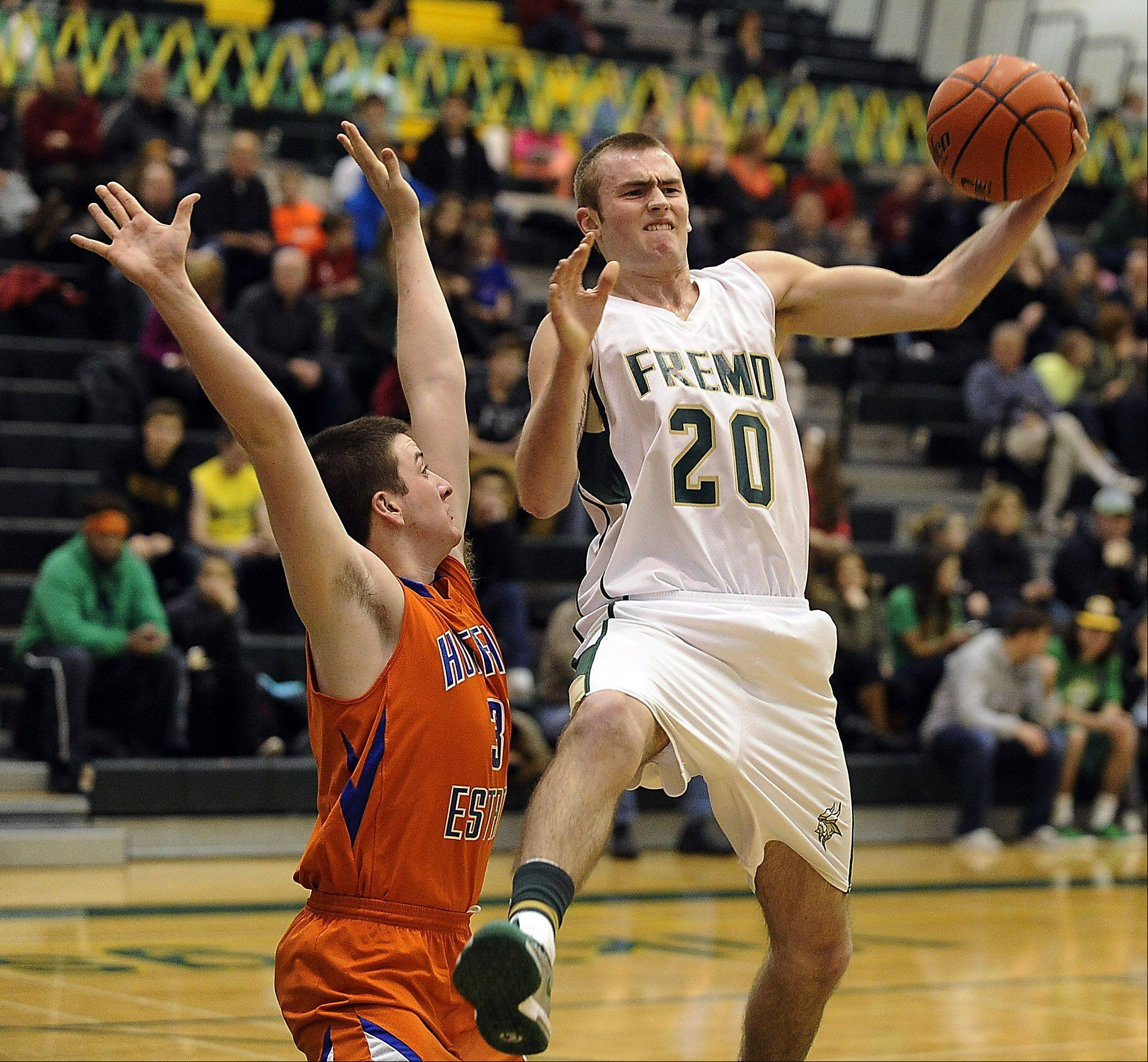 Fremd's Riley Glassmann pulls down a rebound with Hoffman Estates' CJ Conway defending at Fremd on Friday.