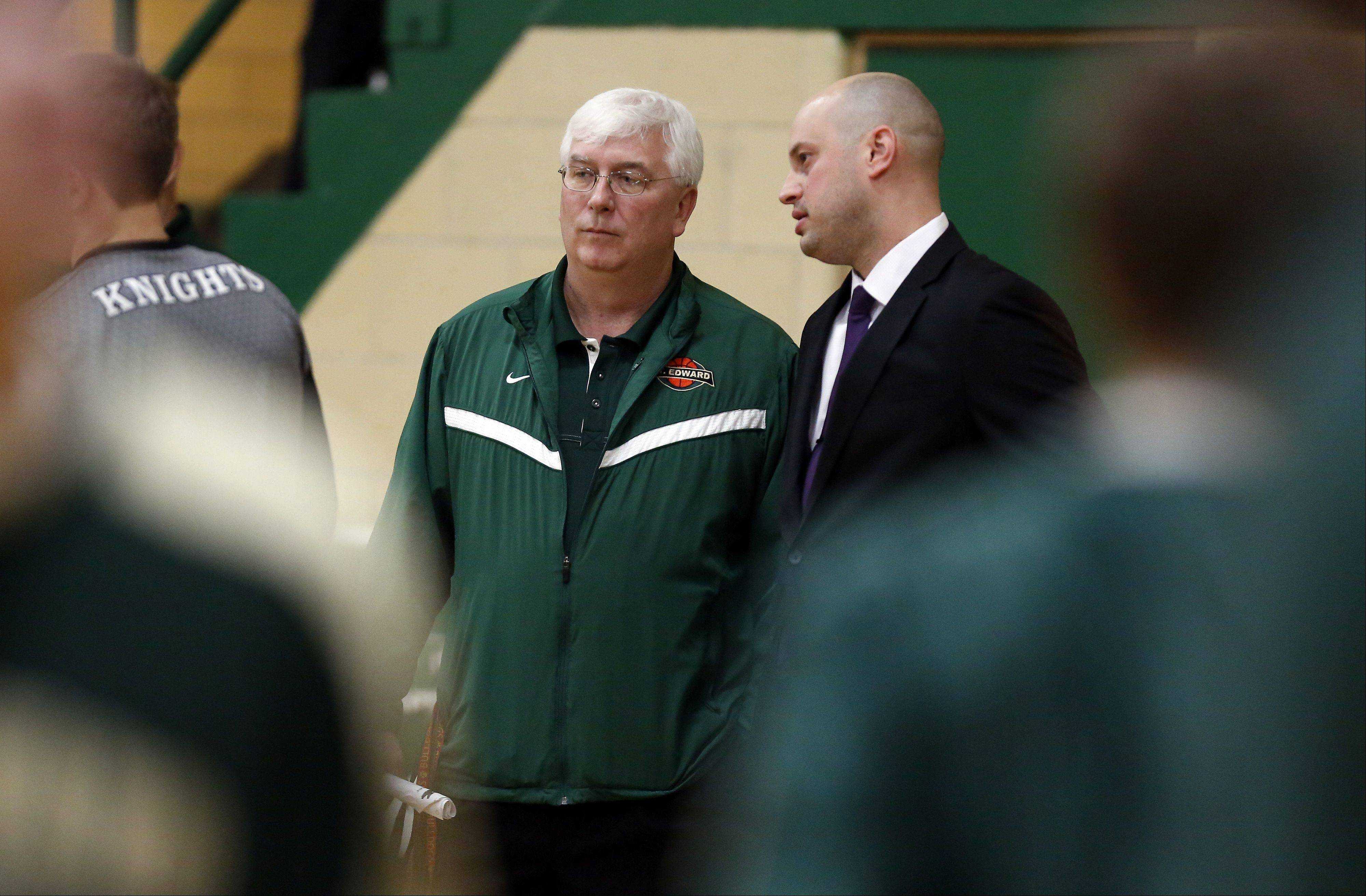 Former St. Edward player and current Kaneland coach Brian Johnson talks to St. Edward coach P.J. White prior to the Kaneland at St. Edward boys basketball game Friday in Elgin.