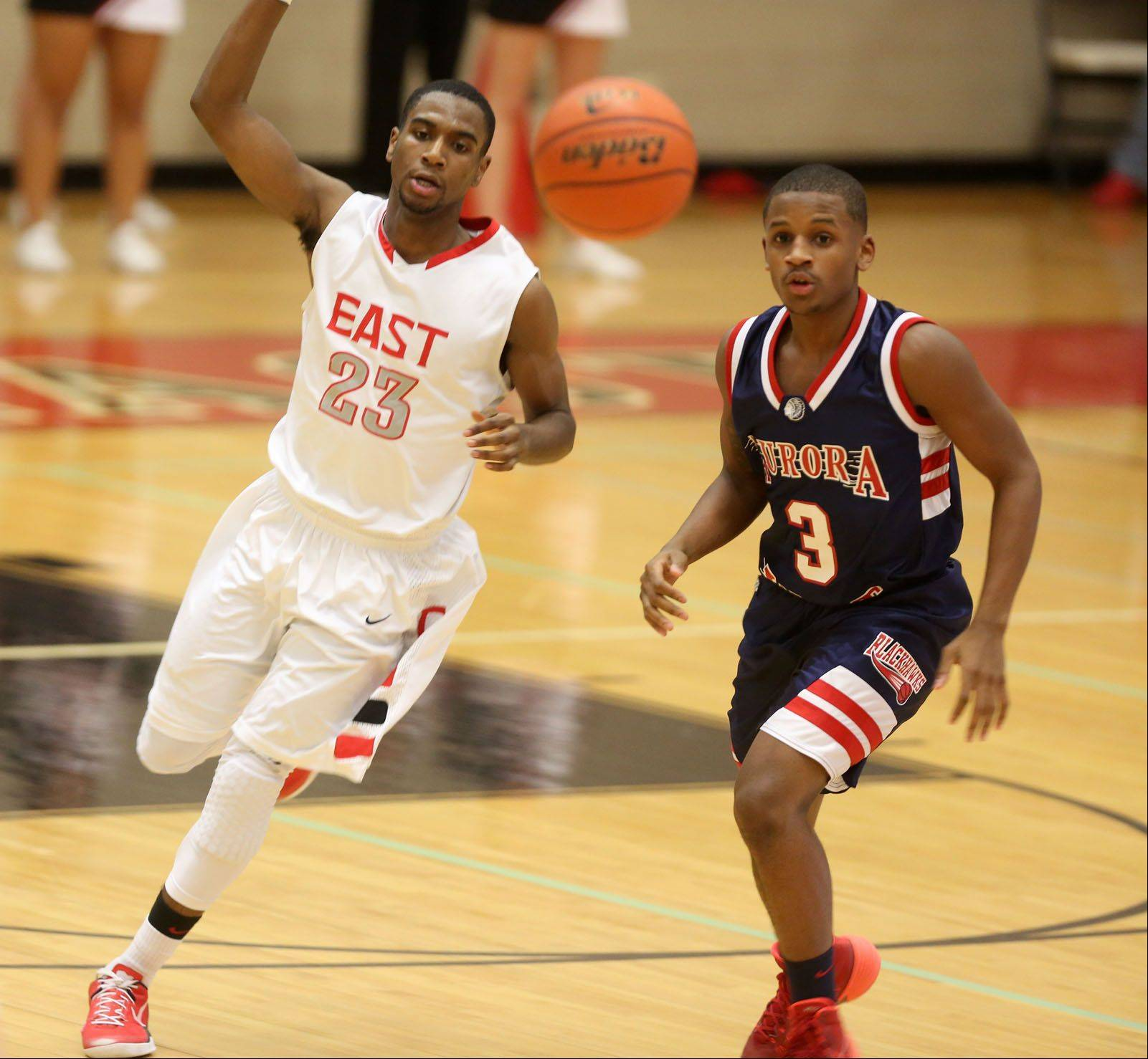 Glenbard East's Jaron Hall moves the ball upcourt against West Aurora.