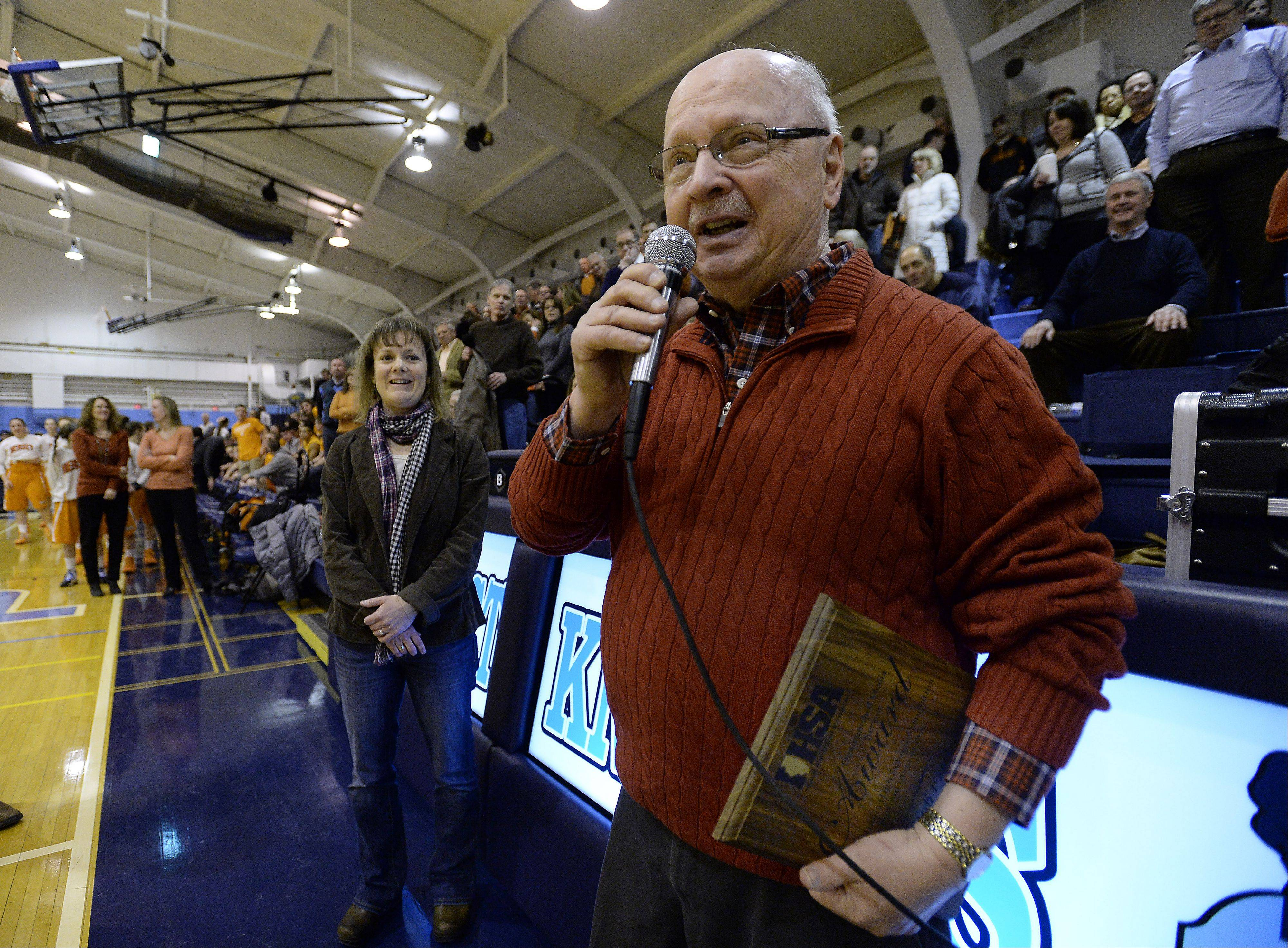 Sports writer Bob Frisk stands with his daughter, Susan Alesia of Madison, Wis., while thanking the crowd at Prospect High School for their support. Frisk is among the first recipients of the IHSA Distinguished Media Service Award presented to him on Friday.