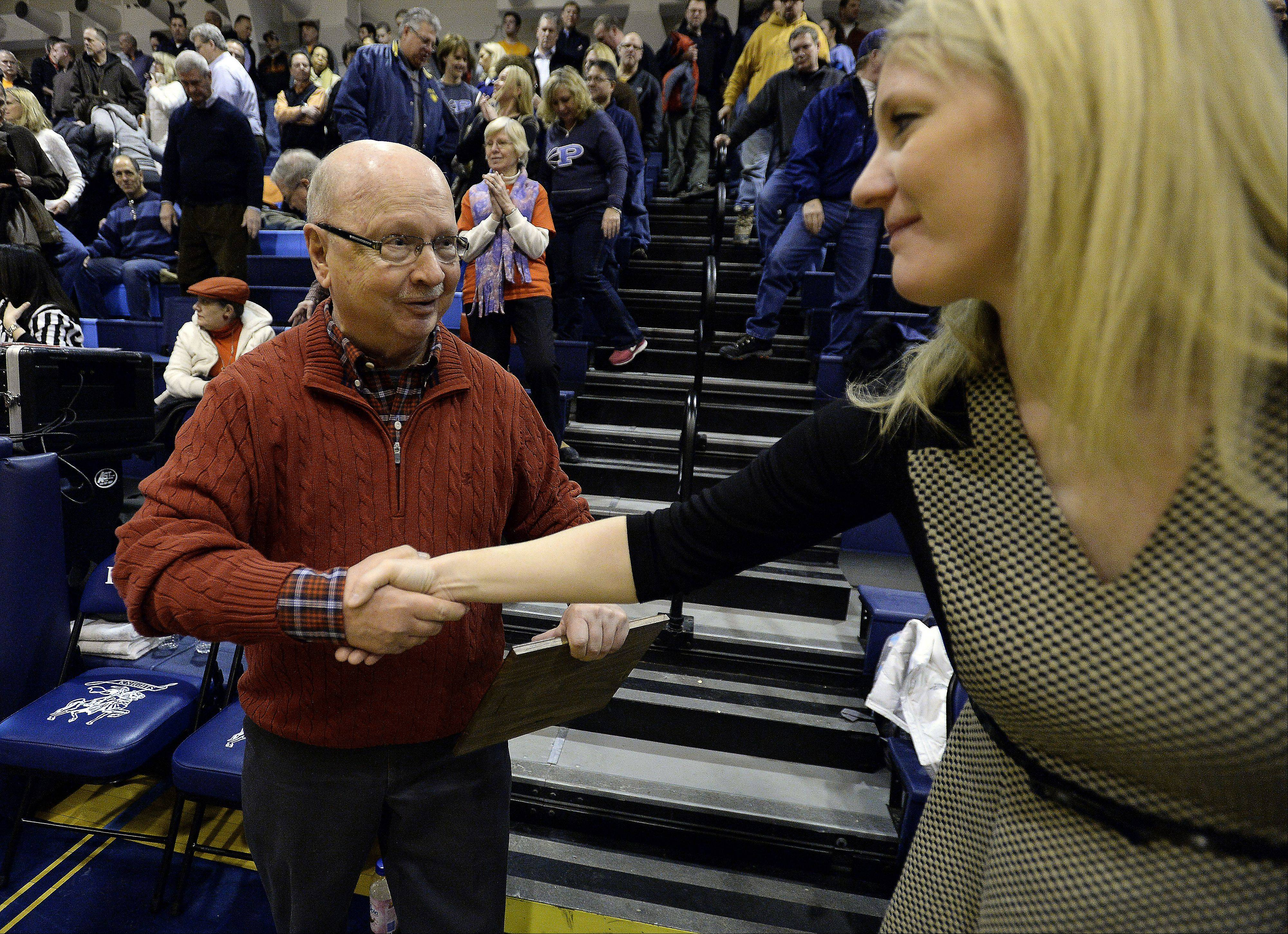 Sports writer Bob Frisk thanks the crowd at Prospect High School for their support during Friday's presentation of the IHSA's Distinguished Media Service Award. Joining him is Prospect girls girls basketball coach Ashley Graham.