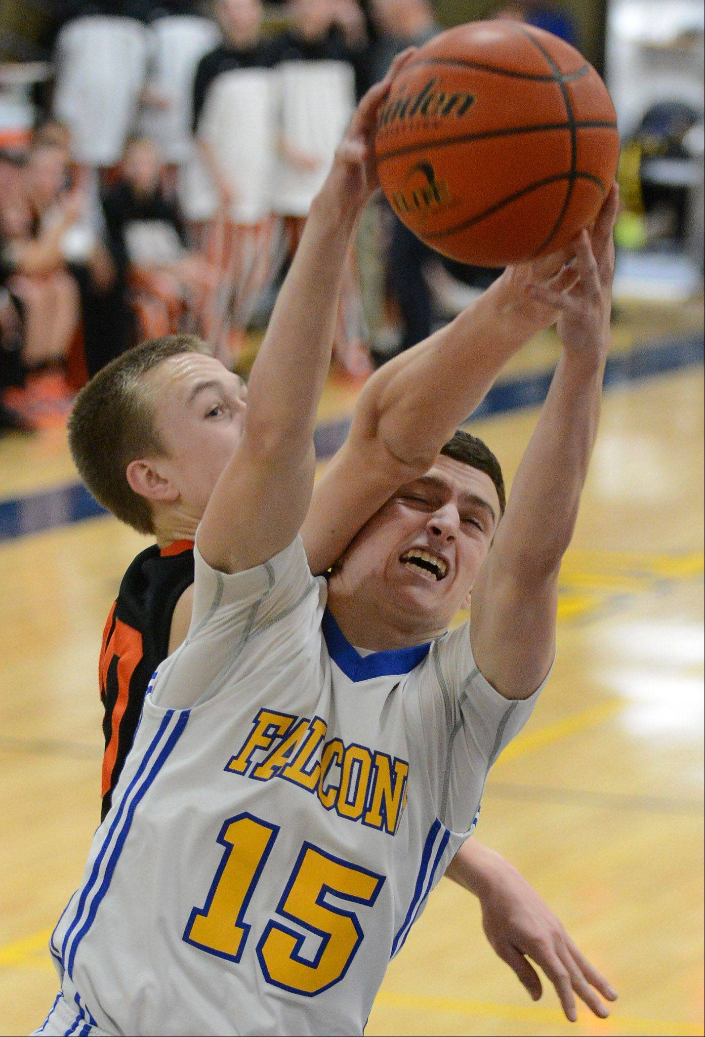 Wheaton North's Nick Jordan grabs a rebound in front of Wheaton Warrenville South's Chris Simpson.