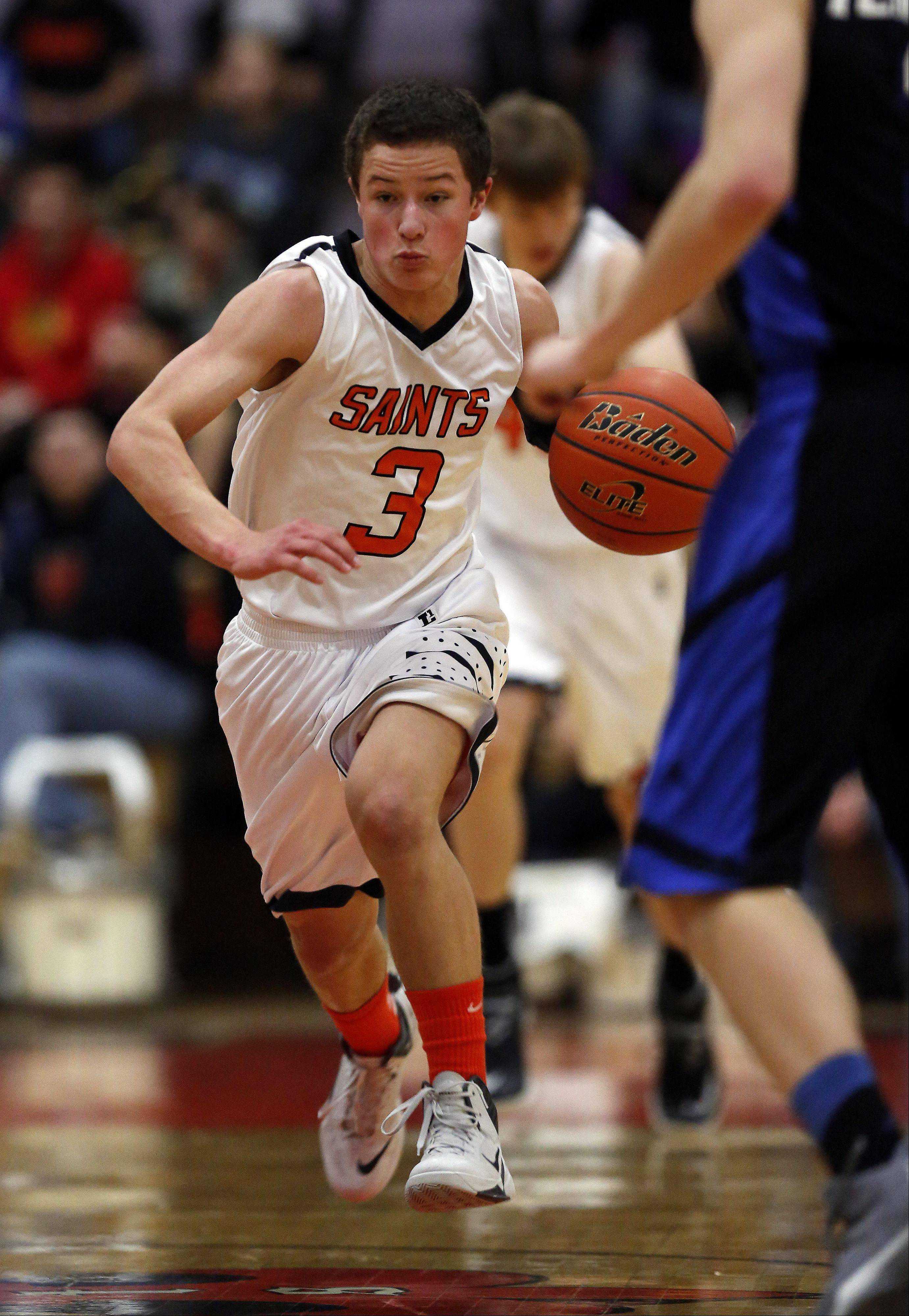 St. Charles East's Cole Gentry, 3, brings the ball up court against Geneva during boys Basketball Saturday.