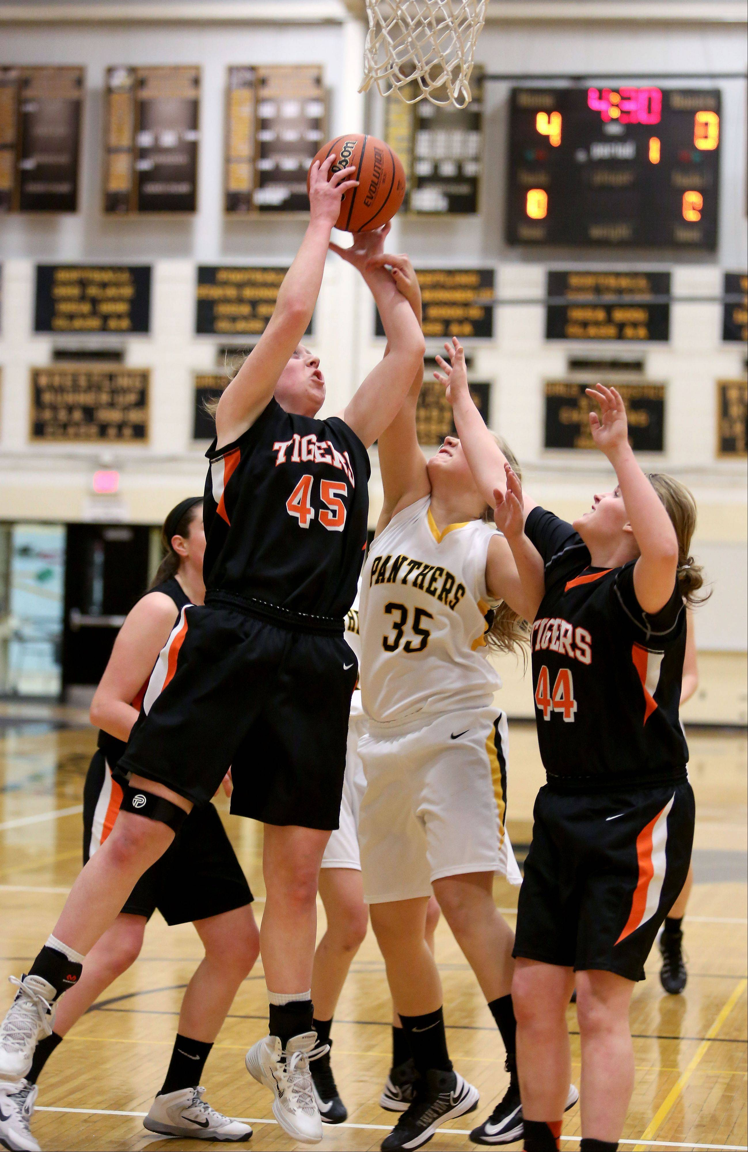 Wheaton Warrenville South's Meghan Waldron, left, gets the rebound from Samantha Yocum of Glenbard North.