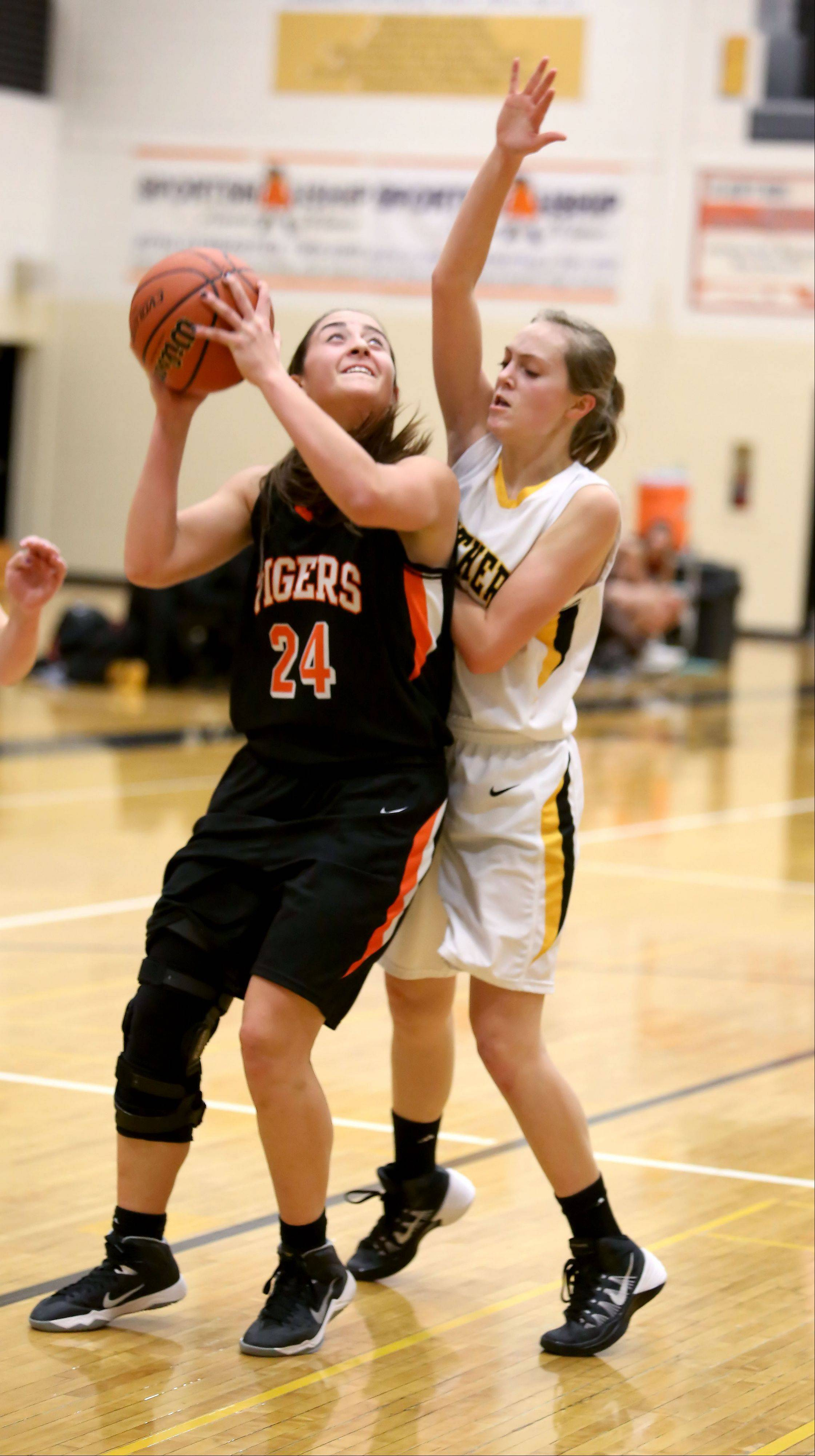 Wheaton Warrenville South's Maggie Dansdill, left, looks to make a basket as Katie Chamberlain of Glenbard North defends.