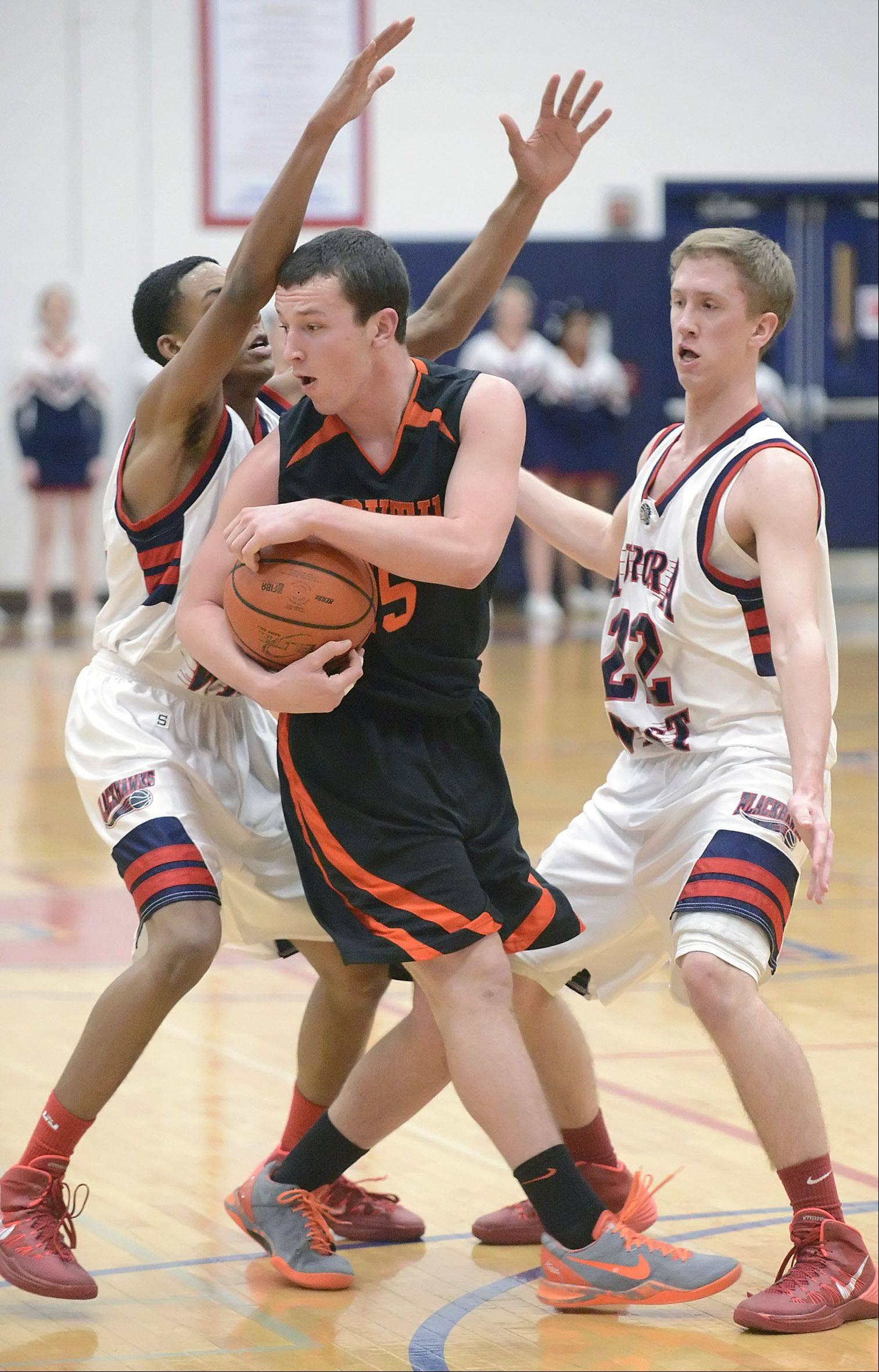 Wheaton Warrenville South's Joe Metzger is swarmed by West Aurora's Antwan Ahamd, left, and Tommy Koth, right, in the third quarter on Tuesday, February 4.