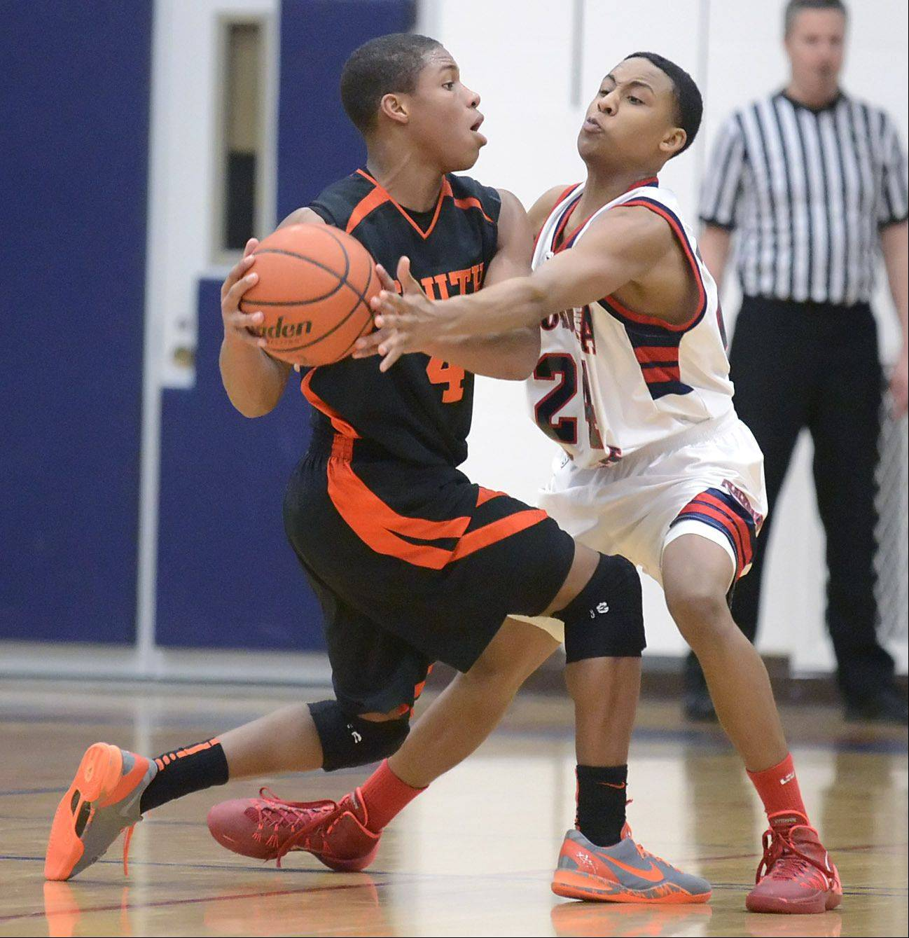 Wheaton Warrenville South's Keishawn Watson tries to pass around a block by West Aurora's Myles Wisley in the second quarter on Tuesday, February 4.