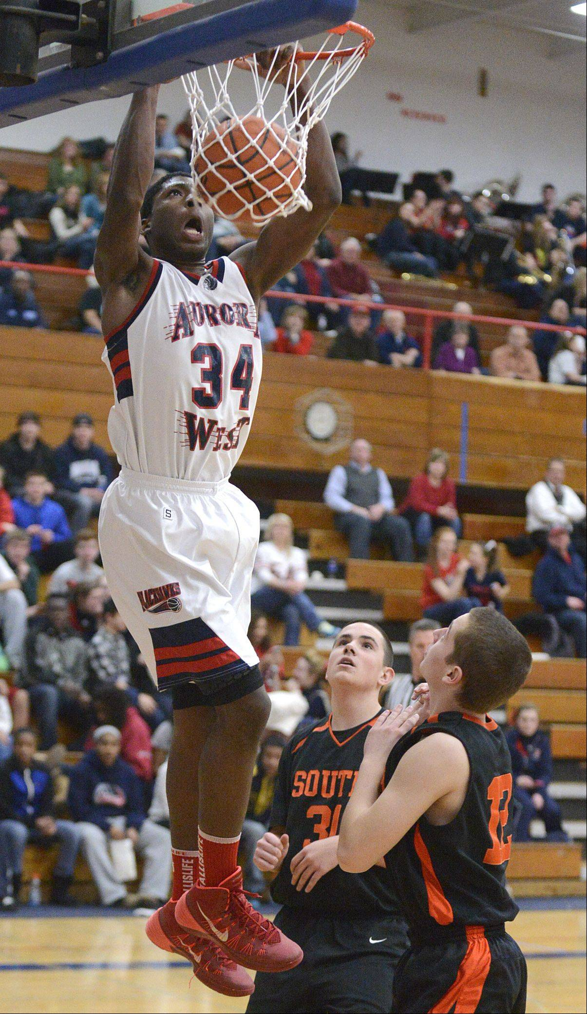 West Aurora's Roland Griffin slam dunks a shot over Wheaton Warrenville South's Austin Polezoes and Brian Summers in the first quarter.