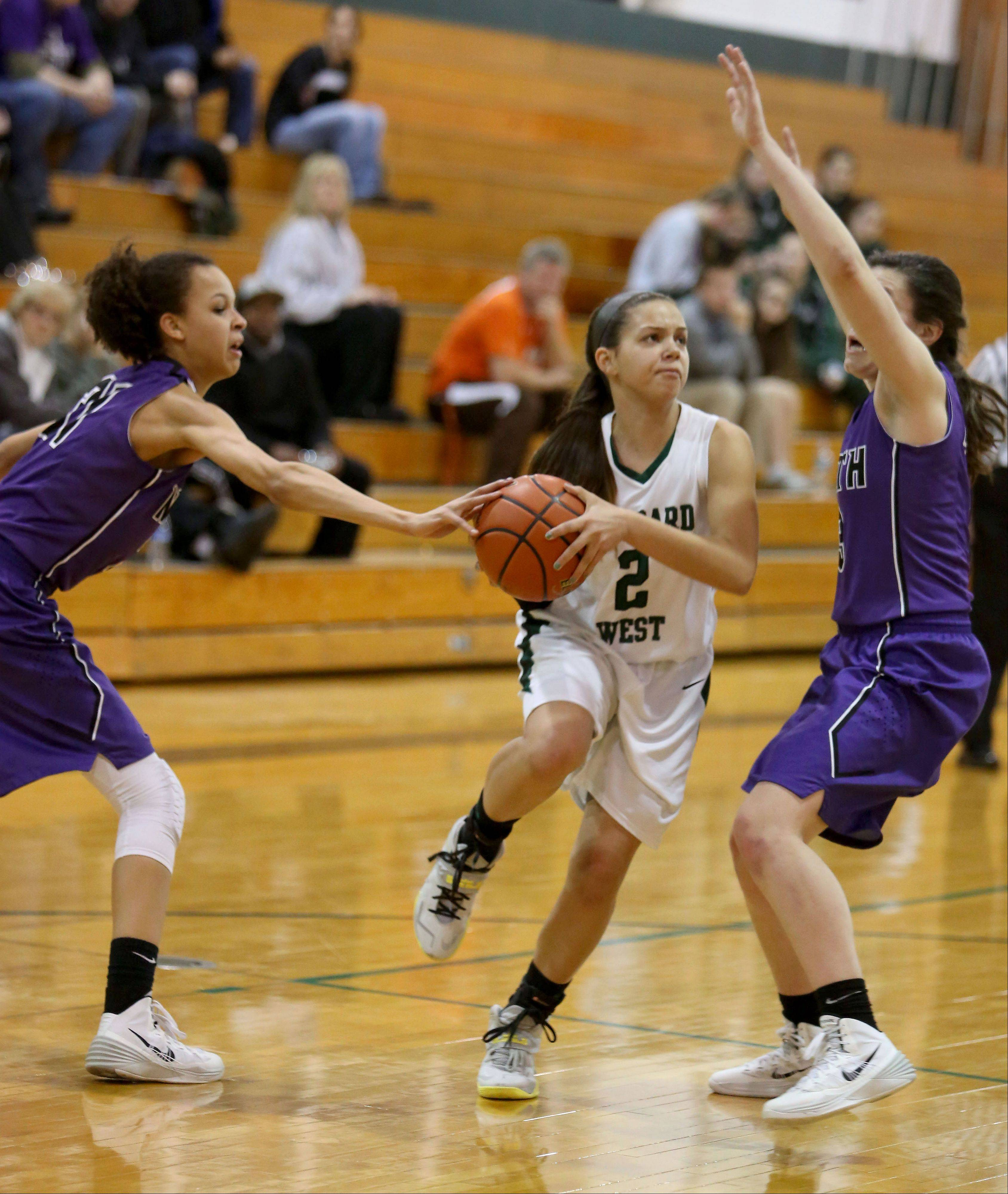 Grey Hayes of Glenbard West, center, moves toward the basket as Jaida Green, left and Sarah Costello of Downers Grove North defend.