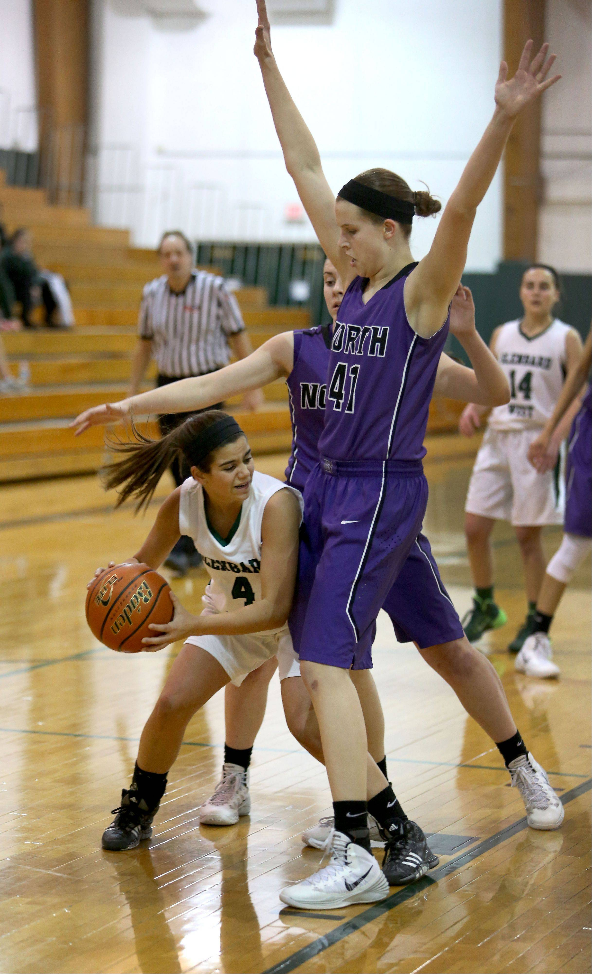 Grace Burrello of Glenbard West, left, looks for room to pass the ball as Peyton Winters of Downers Grove North, right, defends.