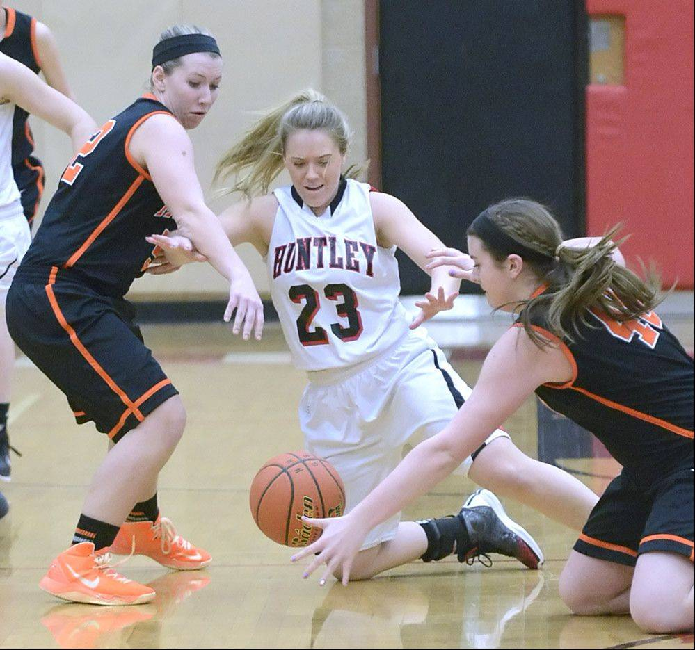 Huntley's Jessica Brock scrambles for a loose ball with McHenry's Gabby Schweitzer, left, and Mckayla Snedker in the first quarter on Wednesday in Huntley.