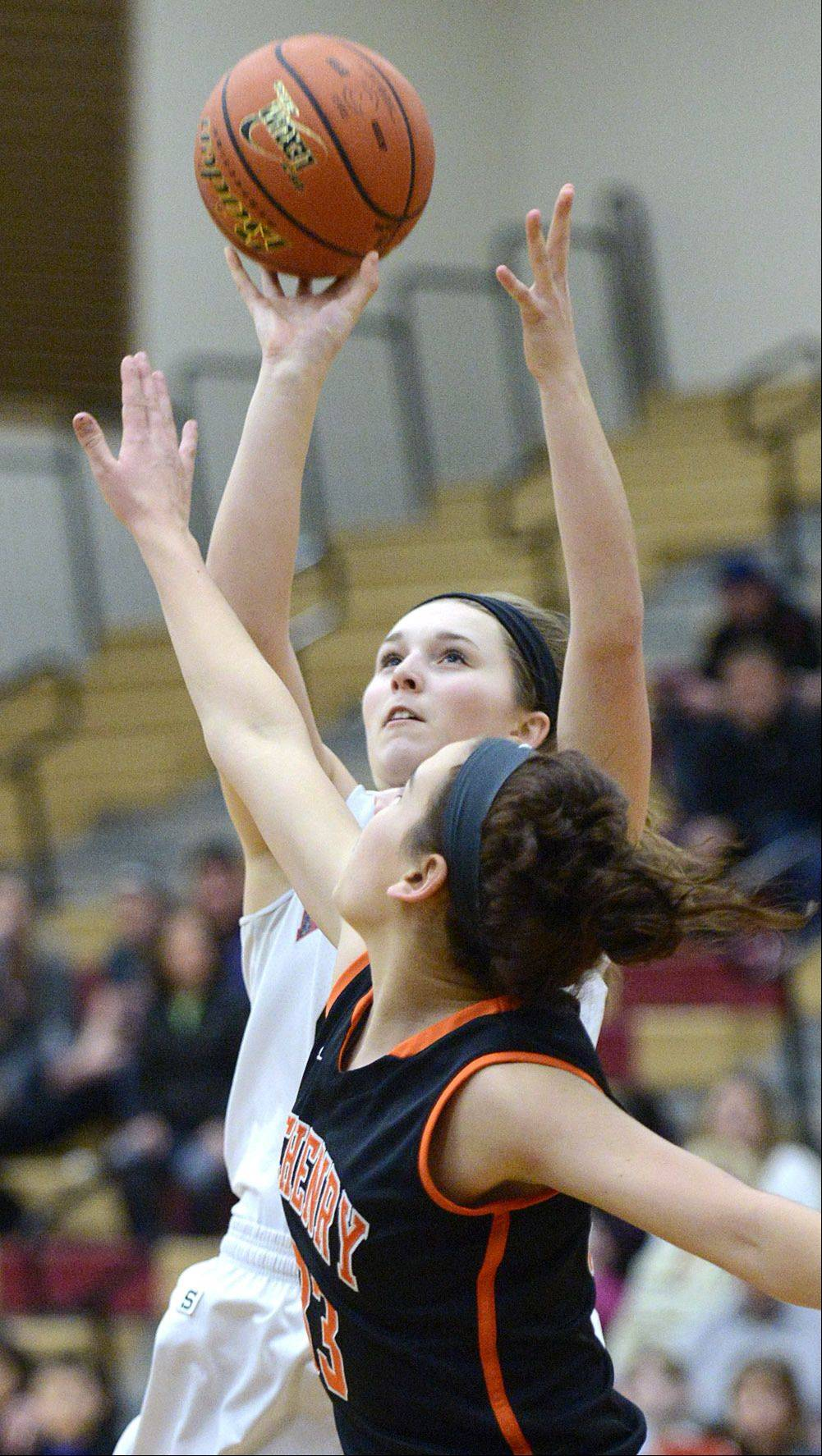 Huntley's Samantha Andrews shoots over a block by McHenry's Alex Martens in the first quarter.