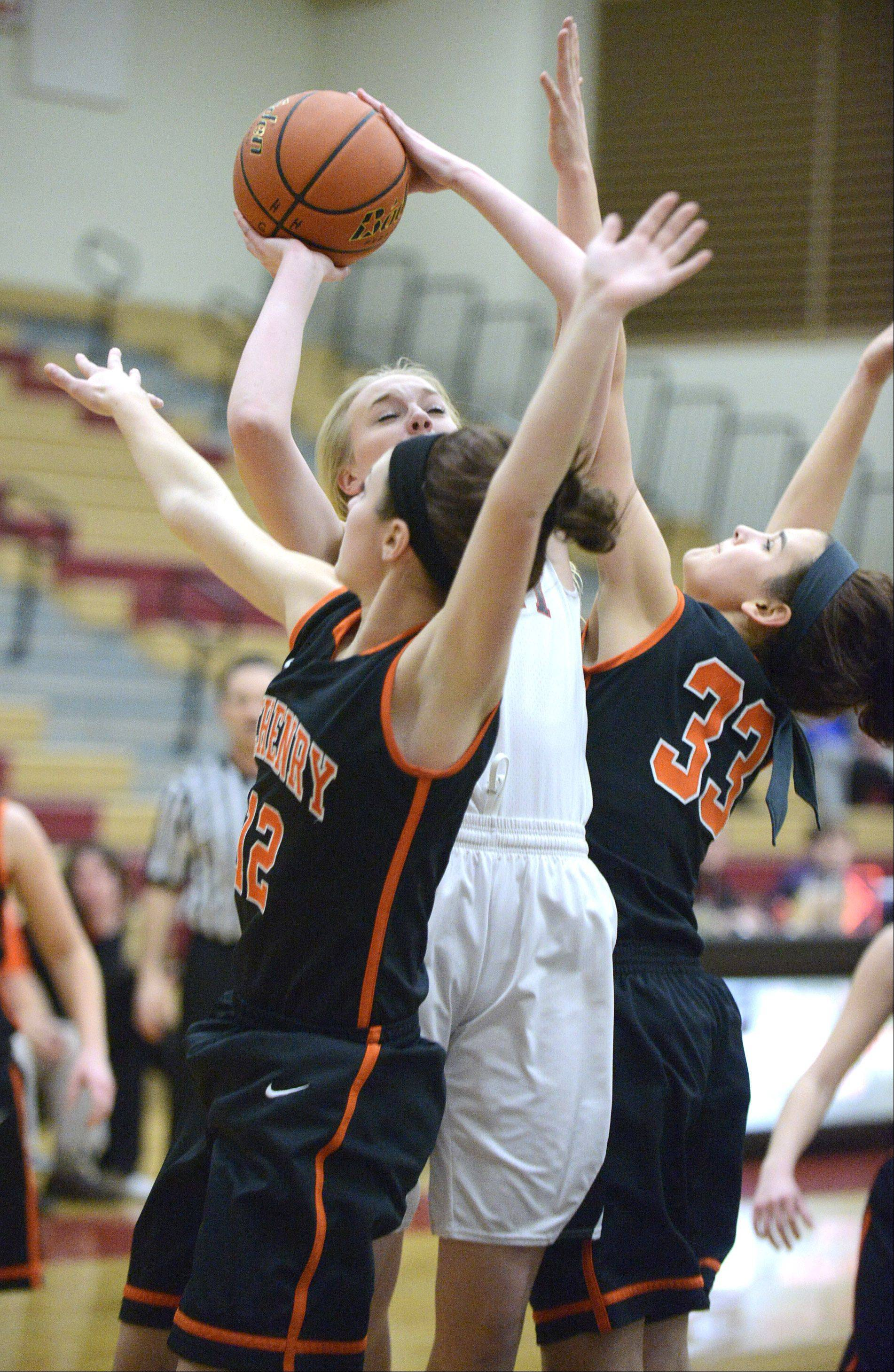 Huntley's Morgan Clausen shoots over a block by McHenry's Gabby Schweitzer, left, and Alex Martens in the second quarter.