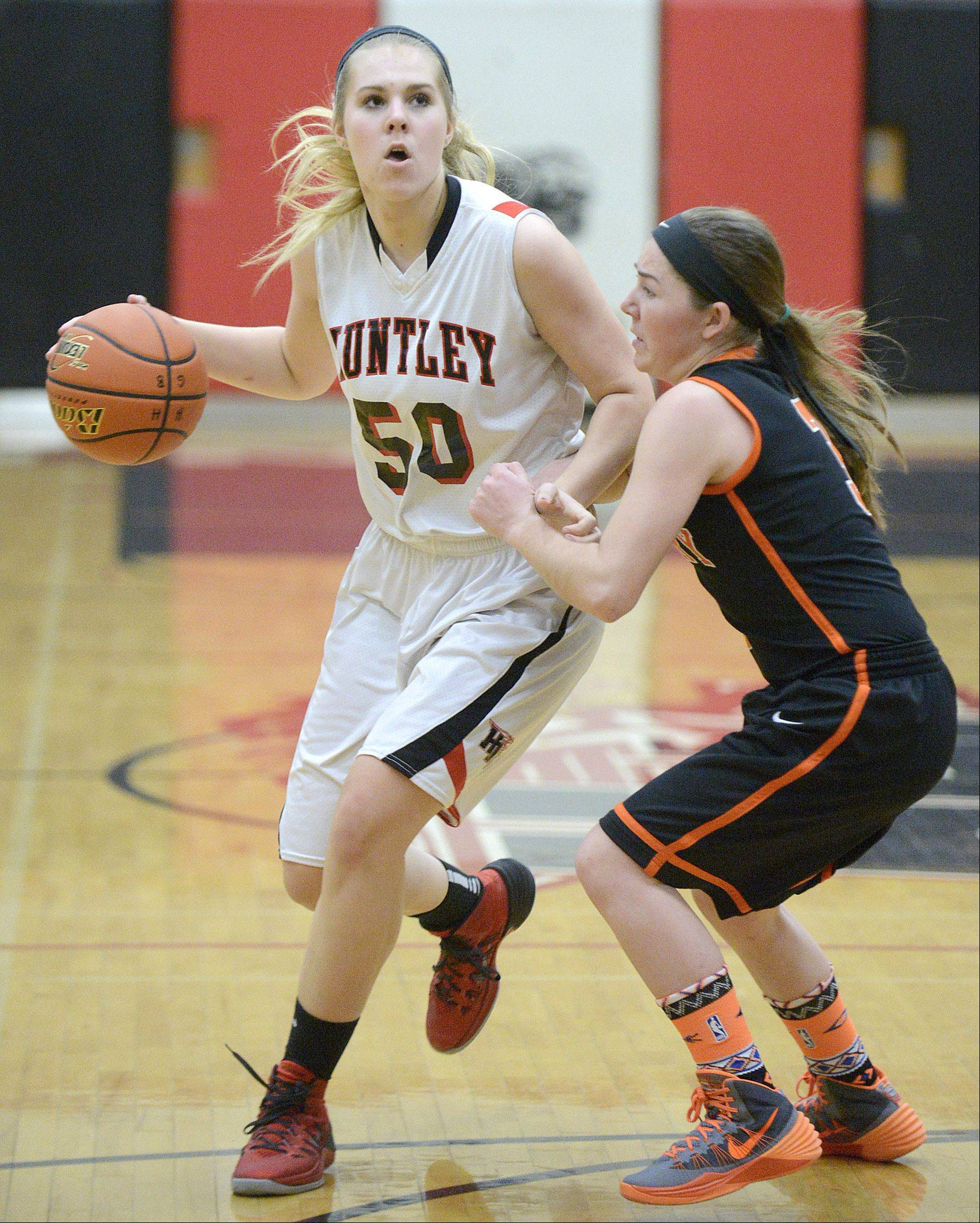 Huntley's Ali Andrews dribbles around McHenry's Carly Mattson in the first quarter.
