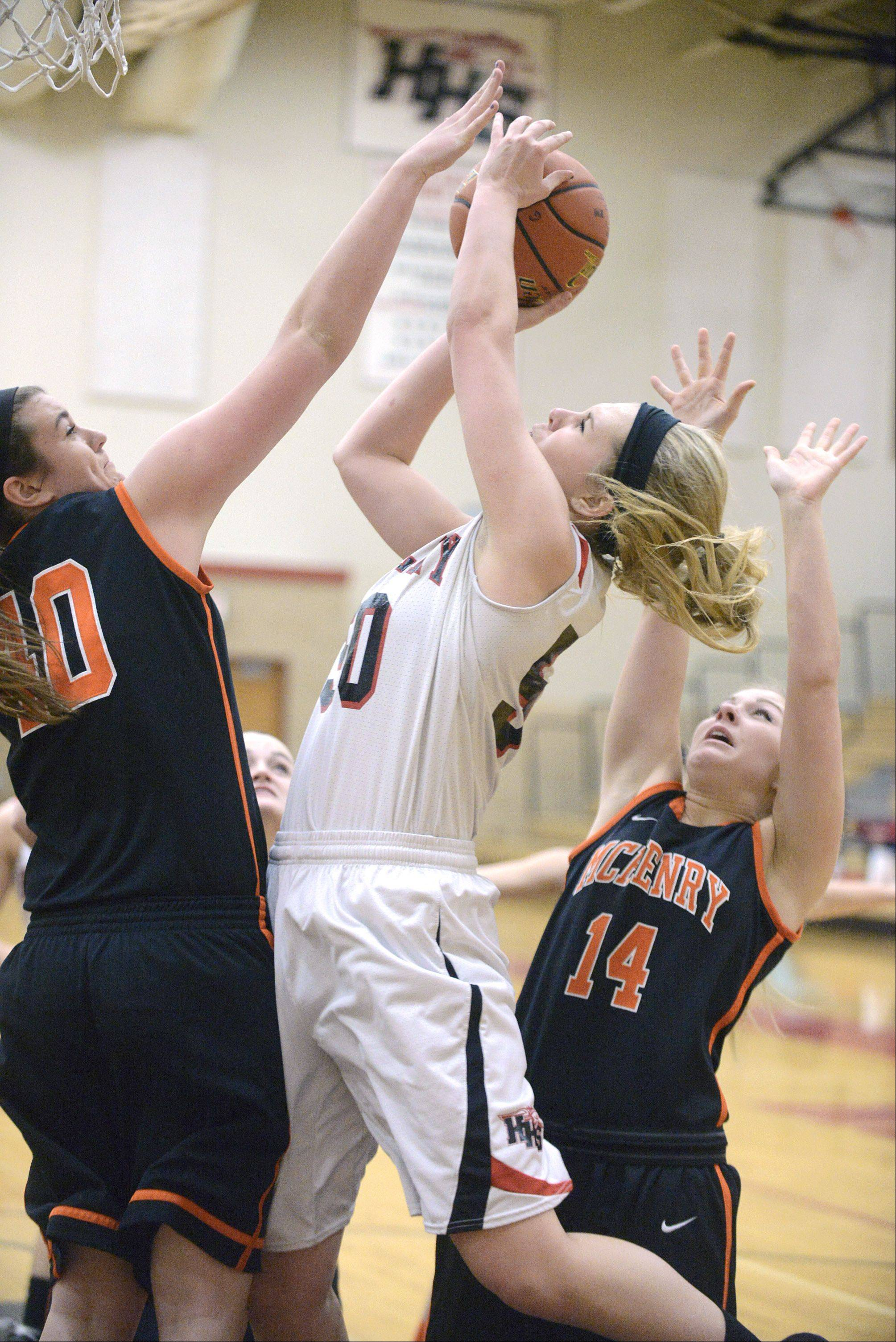 Huntley's Ali Andrews shoots over a block by McHenry's Mckayla Snedeker, left, and Greta Taylor in the first quarter.